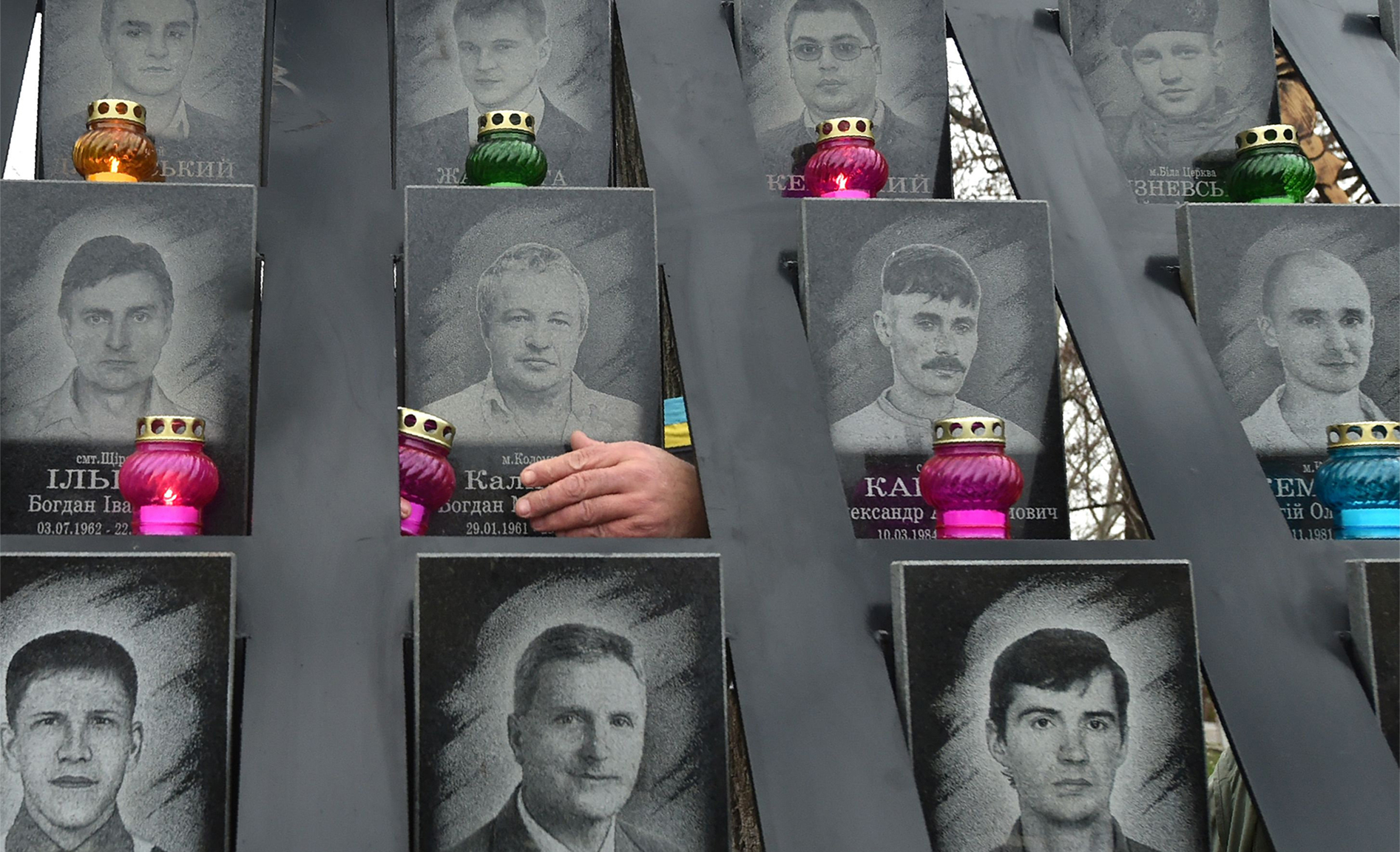 A person touches a portrait at the memorial for died Maidan activists