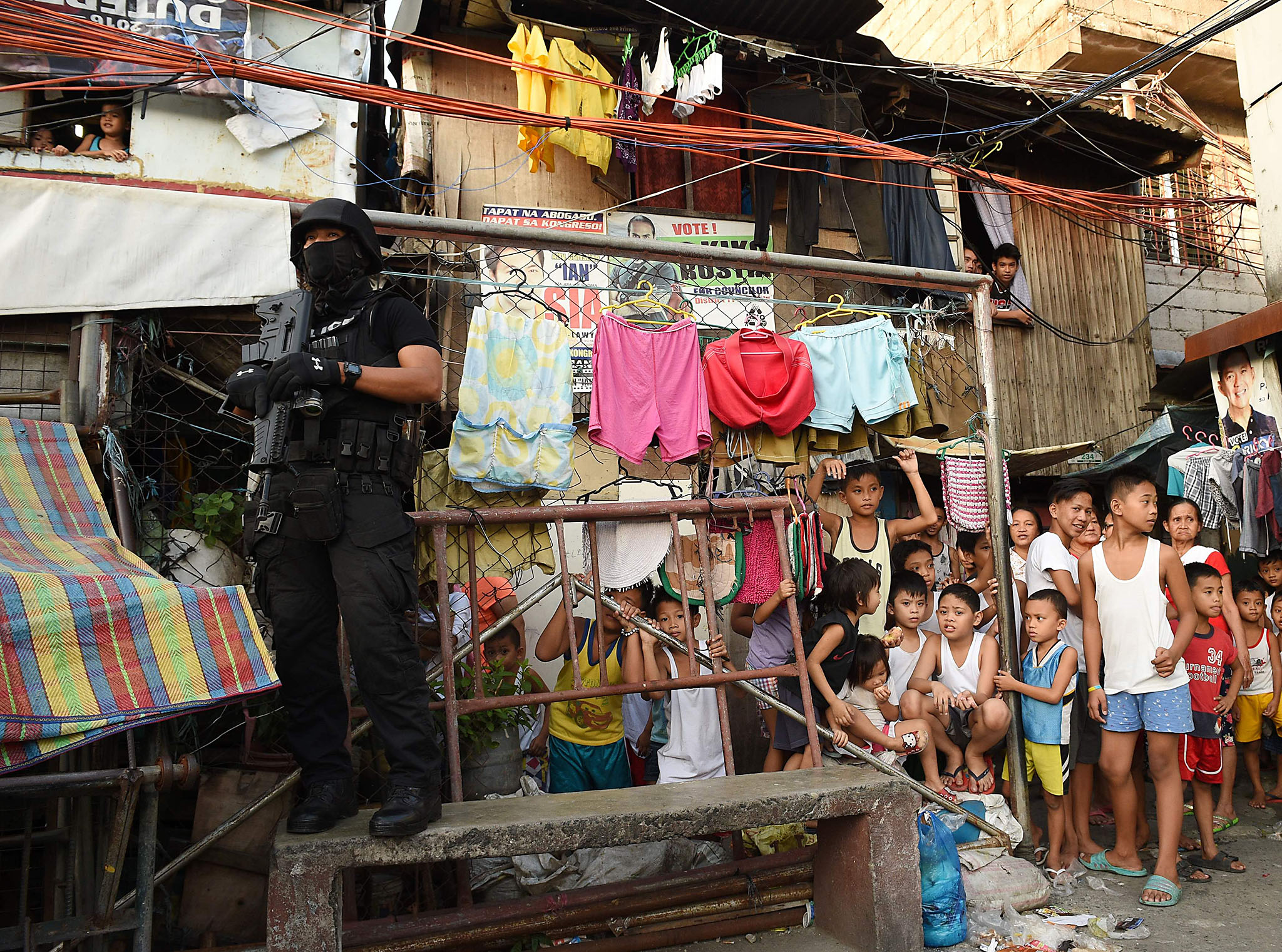 A member of the Special Weapons and Tactics (SWAT) team stands guard as residents look on during an anti-drug operation at an informal settlers area in Manila on November 9, 2016.  Since President Rodrigo Duterte took office on June 30, his war on drugs and other crimes has claimed more than 4,100 lives, according to official figures. / AFP PHOTO / TED ALJIBETED ALJIBE/AFP/Getty Images