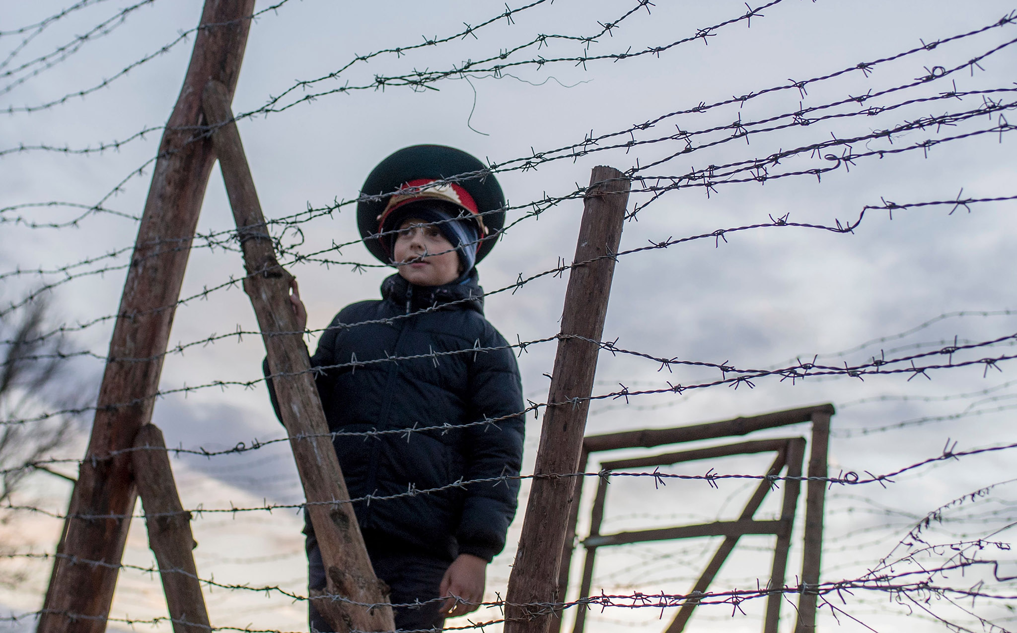 Matus, a seven-year-old Slovak boy, wears a Soviet military hat as he stands by remains of the border fences from the former 'Iron curtain' between Slovakia and Austria on November 20,2016 near Bratislava, Slovakia.  The bridge was symbolically closed for 3 days to remeber victims who lost their lives trying to escape the communist regime. Slovaks and Czechs commemorated on 17 of November 26th anniversary of the Velvet revolution. / AFP PHOTO / JOE KLAMARJOE KLAMAR/AFP/Getty Images