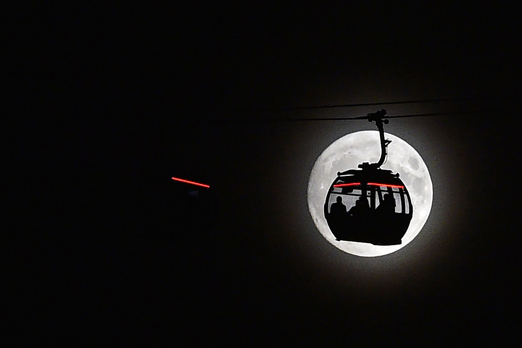 The moon rises behind a car on the The Emirates Air Line (cable car) in London's Docklands on November 13, 2016. Tomorrow, the moon will orbit closer to the earth than at any time since 1948, named a 'supermoon', it is defined by a Full or New moon coinciding with the moon's closest approach to the Earth. / AFP PHOTO / Glyn KIRKGLYN KIRK/AFP/Getty Images