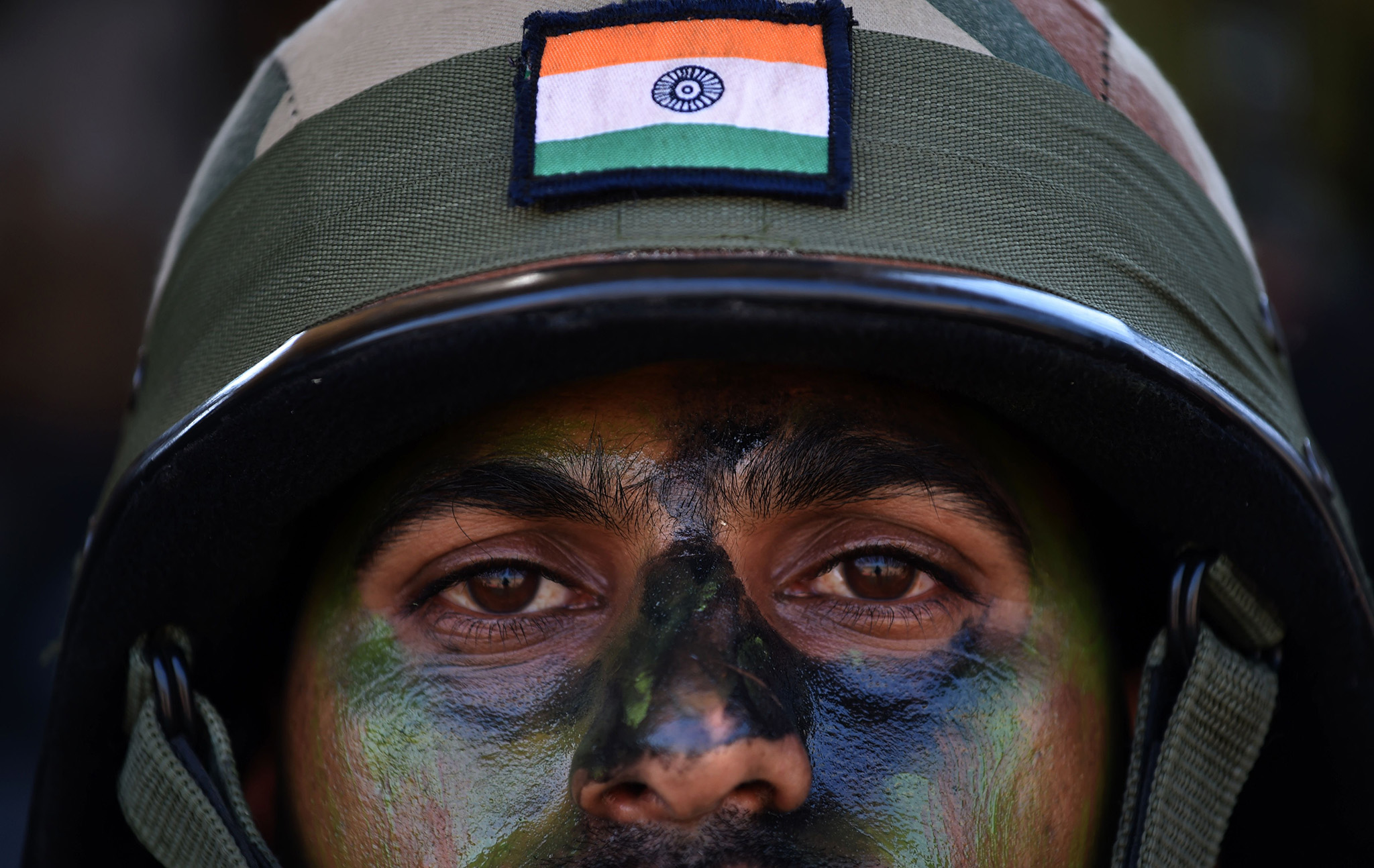 "An Indian Army soldier sits with soldiers of the People's Liberation Army (PLA) of China after participating in an anti-terror drill during the Sixth India-China Joint Training exercise ""Hand in Hand 2016"" at HQ 330 Infantry Brigade, in Aundh in Pune district, some 145km southeast of Mumbai, on November 25, 2016. / AFP PHOTO / INDRANIL MUKHERJEEINDRANIL MUKHERJEE/AFP/Getty Images"