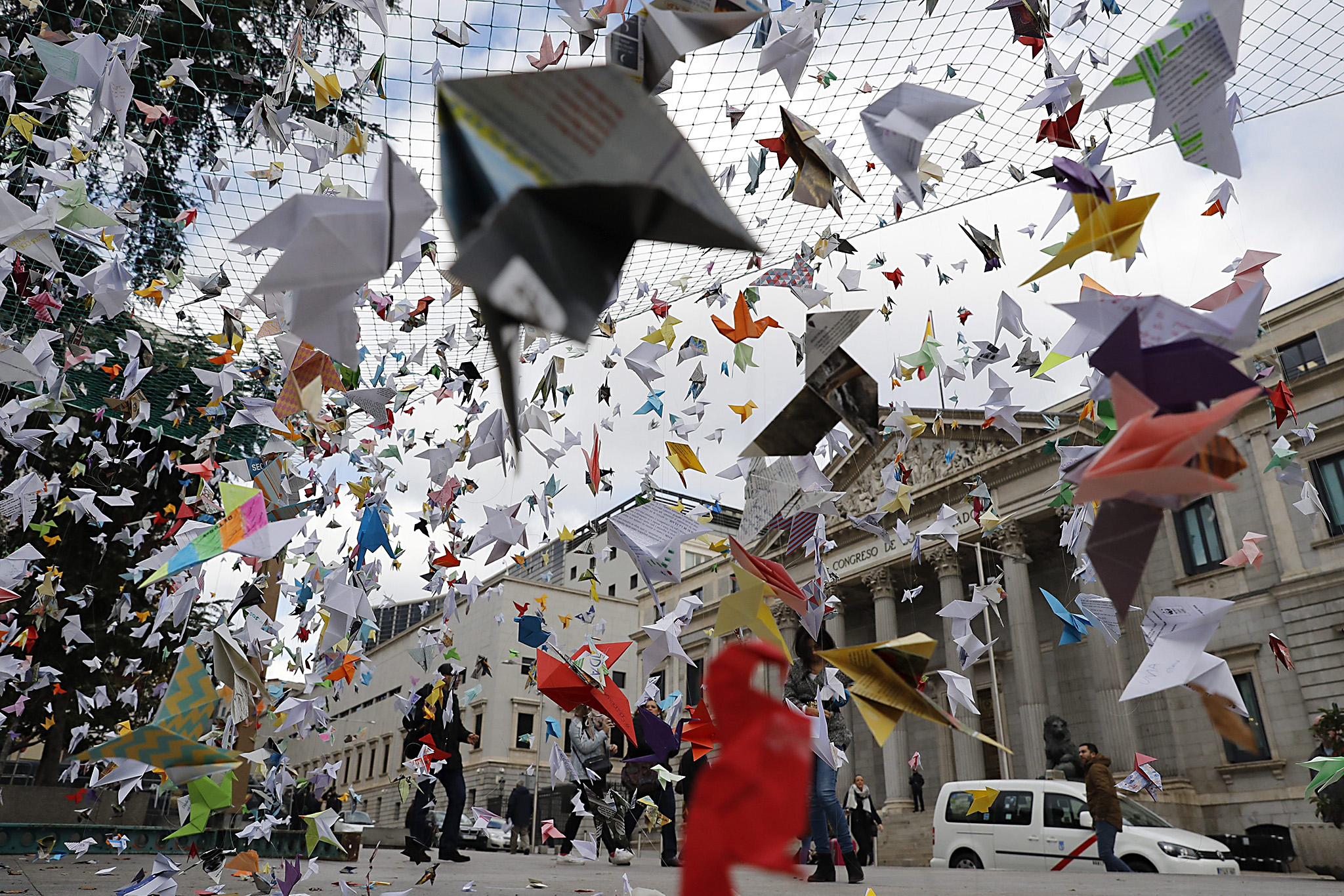 epa05645016 Pedestrians walk past paper birds placed by WWF activists opposite the Spanish Lower House in Madrid, Spain, 24 November 2016, to demand a stronger protection of the Spanish National Park Donana in Andalucia.  EPA/JUAN CARLOS HIDALGO