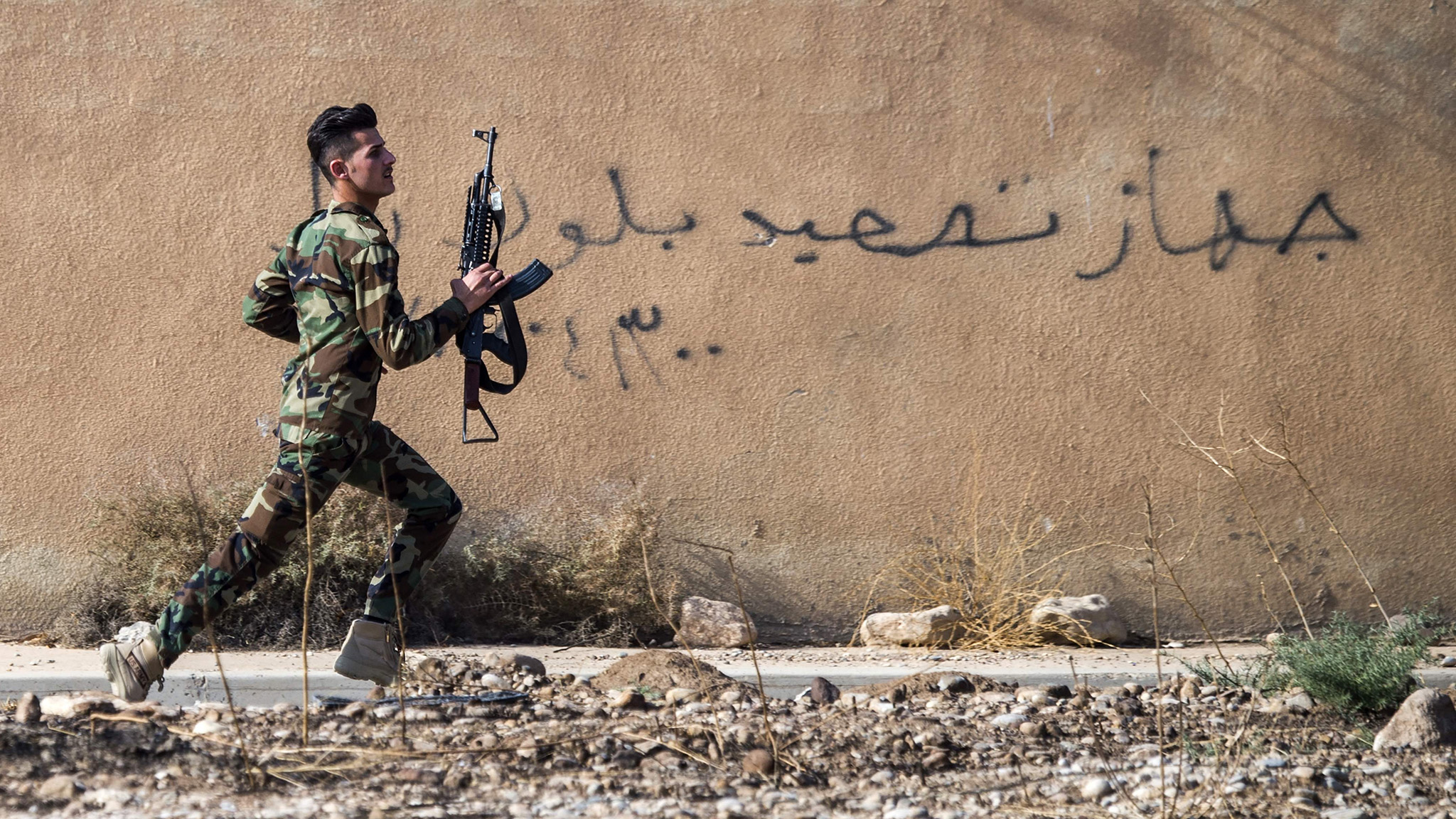 "A Peshmerga fighter runs to take position as the Iraqi Kurdish forces pushed deeper into the town of Bashiqa during street battles against Islamic State (IS) group jihadists on November 8, 2016.  Capturing Bashiqa would be one of the final steps in securing the eastern approaches to Mosul, three weeks into an offensive by Iraqi forces to retake the country's second city. The town was under the ""complete control"" of Kurdish peshmerga forces, Jabbar Yawar, the secretary general of the Kurdish regional ministry responsible for the fighters, told AFP. / AFP PHOTO / Odd ANDERSENODD ANDERSEN/AFP/Getty Images"