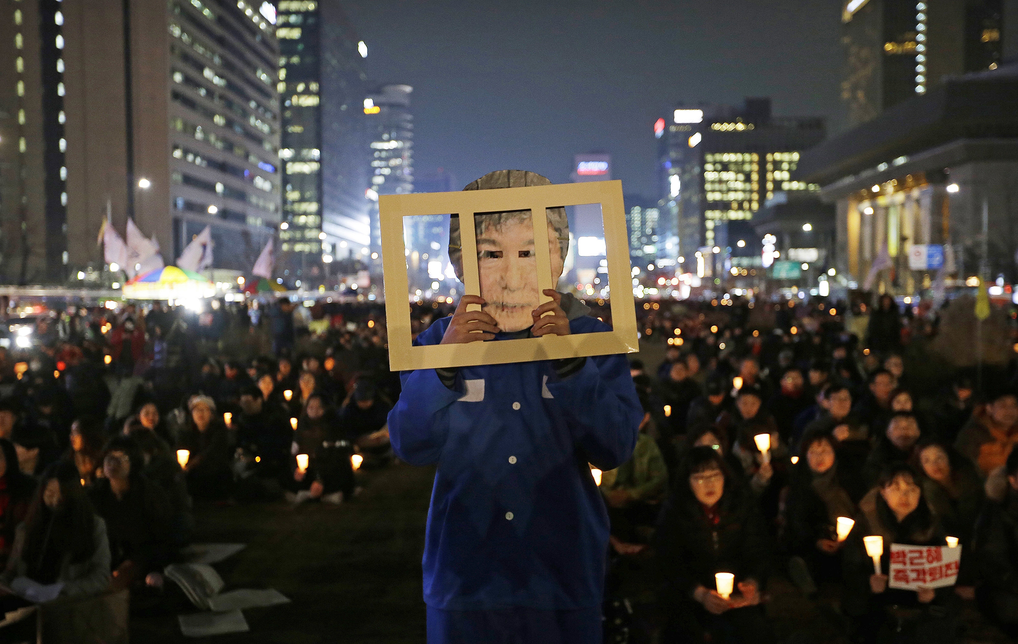 A protester wearing a mask of South Korean President Park Geun-hye performs during a rally calling for Park to step down in Seoul, South Korea, Wednesday, Nov. 30, 2016. South Korean President Park Geun-hye's conditional resignation offer appears to be causing cracks in what previously had been a strong push for her impeachment, with opponents now struggling to set a date for a vote to strip her of power. (AP Photo/Ahn Young-joon)