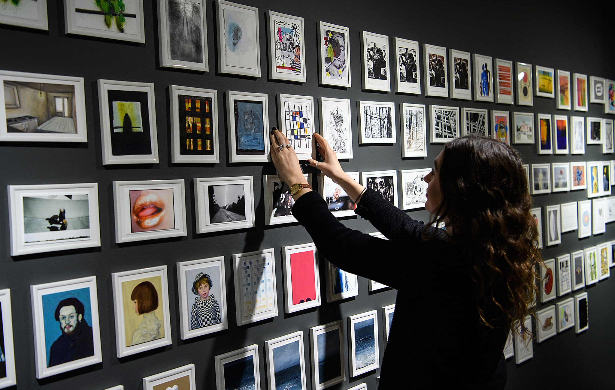 A member of staff poses next to some of the 400 postcards by various artists including Damien Hirst and Grayson Perry on display ahead of a secret auction, at the Maddox Gallery on November 15, 2016 in London, England. The auction takes place at the Bloomsbury Auction House on November 17 and is raising funds for the Hepatitis C Trust.  (Photo by Carl Court/Getty Images)