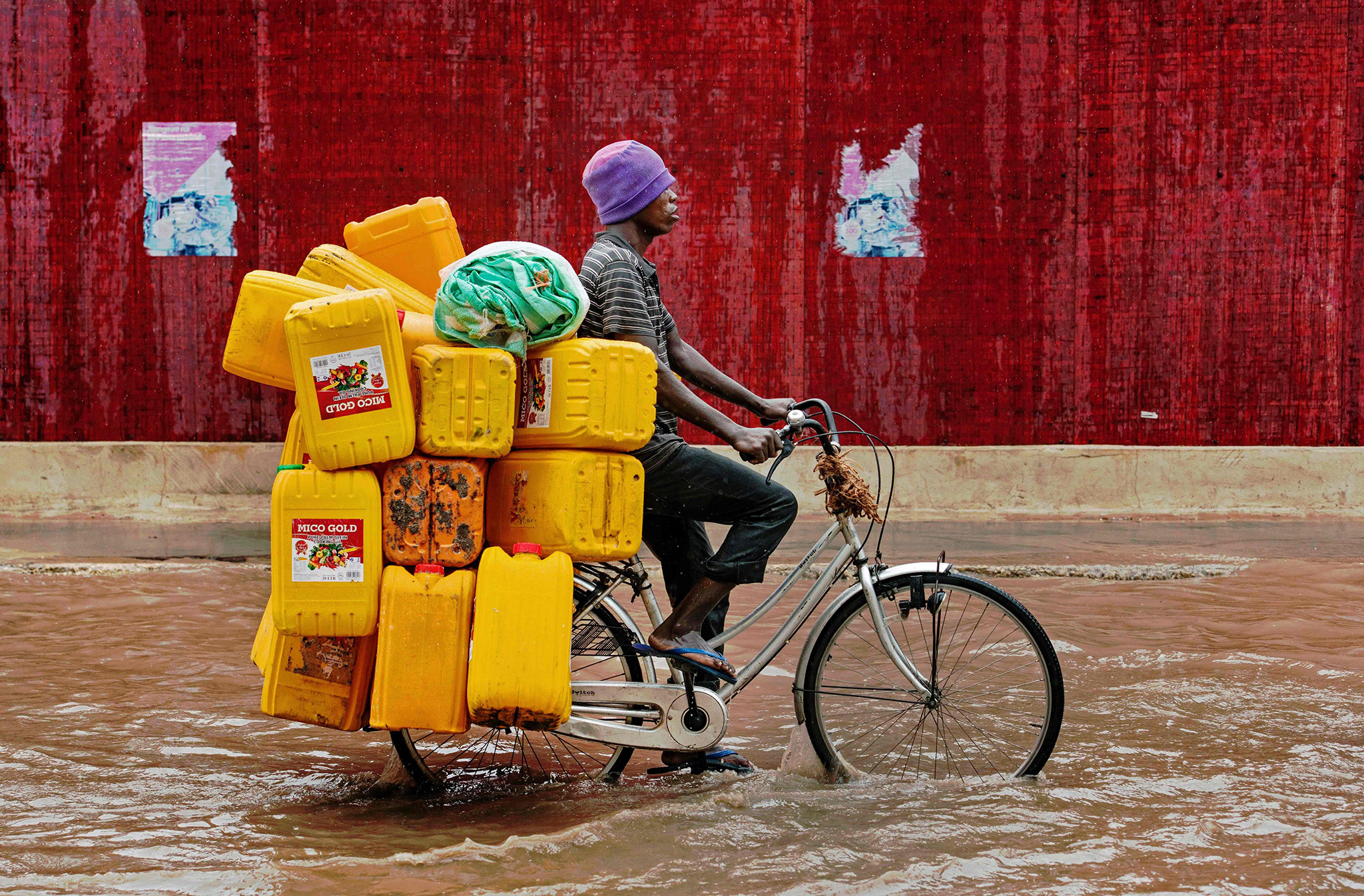 A man bicycles down a flooded street with empty cooking oil containers during a rain storm in Dar es Salaam, Tanzania on November 23, 2016. / AFP PHOTO / DANIEL HAYDUKDANIEL HAYDUK/AFP/Getty Images