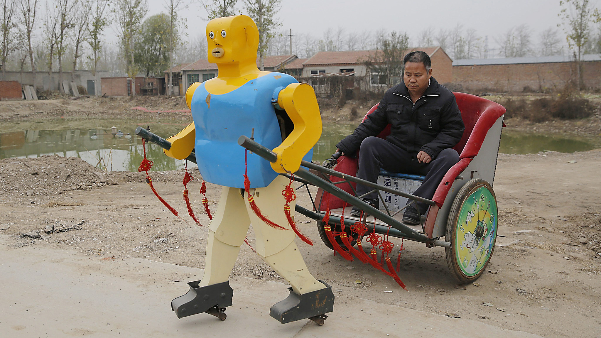 Robot inventor Wu Yulu sits on a rickshaw driven by a robot which he invented in his village in rural Beijing's Tongzhou district, China, 17 November 2016. The 54-year-old Chinese farmer living in rural Beijing's Tongzhou district invented 63 robots in the past 30 years. Wu, who only received primary school education, plans to give up the agricultural work for his robot products. He regularly participates in exhibitions, transfers patent rights and teaches at the university to earn money.  EPA/WU HONG