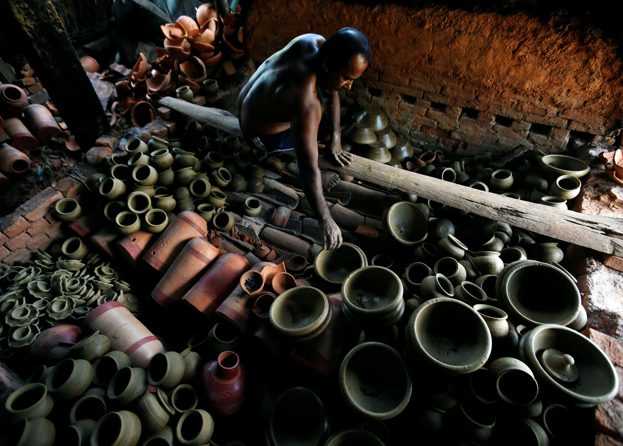 A man places newly made clay pots in a fire pit at a workshop in Biyagama, Sri Lanka November 16, 2016. REUTERS/Dinuka Liyanawatte