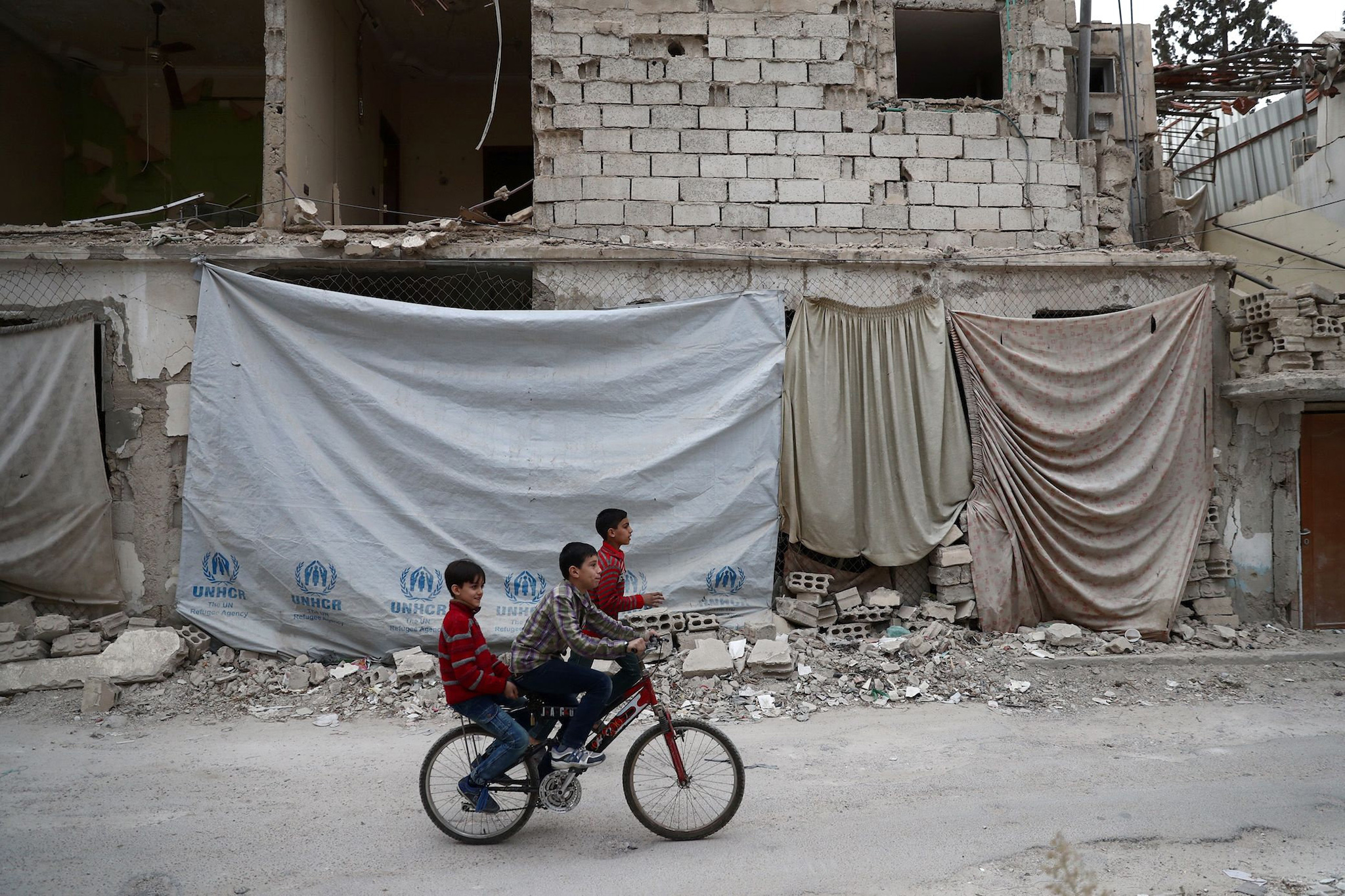 Syrian children ride a bicycle in the rebel-held town of Douma on the eastern outskirts of the capital Damascus on November 13, 2016. Douma, the largest town in the Eastern Ghouta area with more than 100,000 residents, is surrounded and regularly shelled by regime forces. / AFP PHOTO / Abd DoumanyABD DOUMANY/AFP/Getty Images