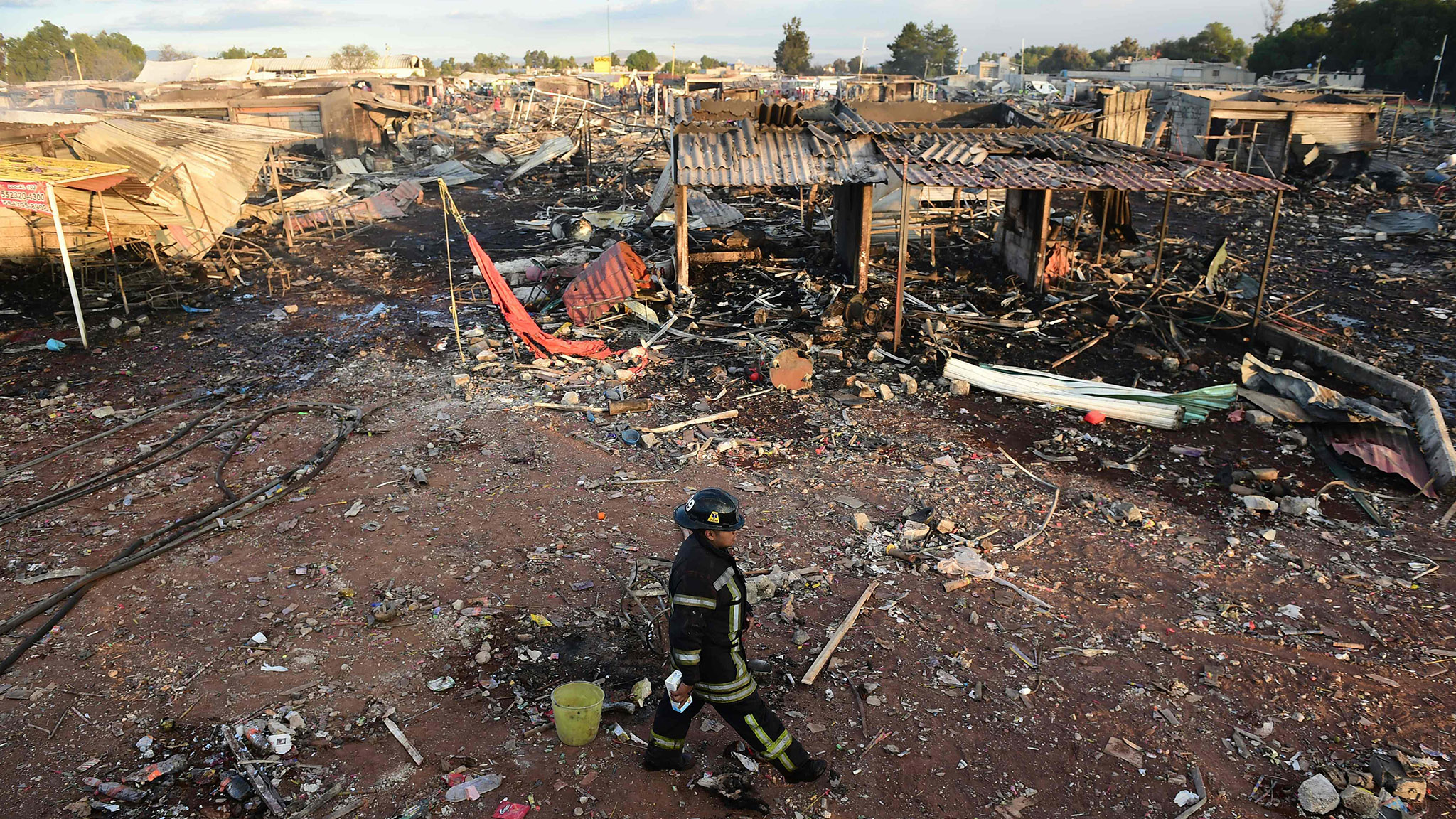 Firefighters work amid the debris