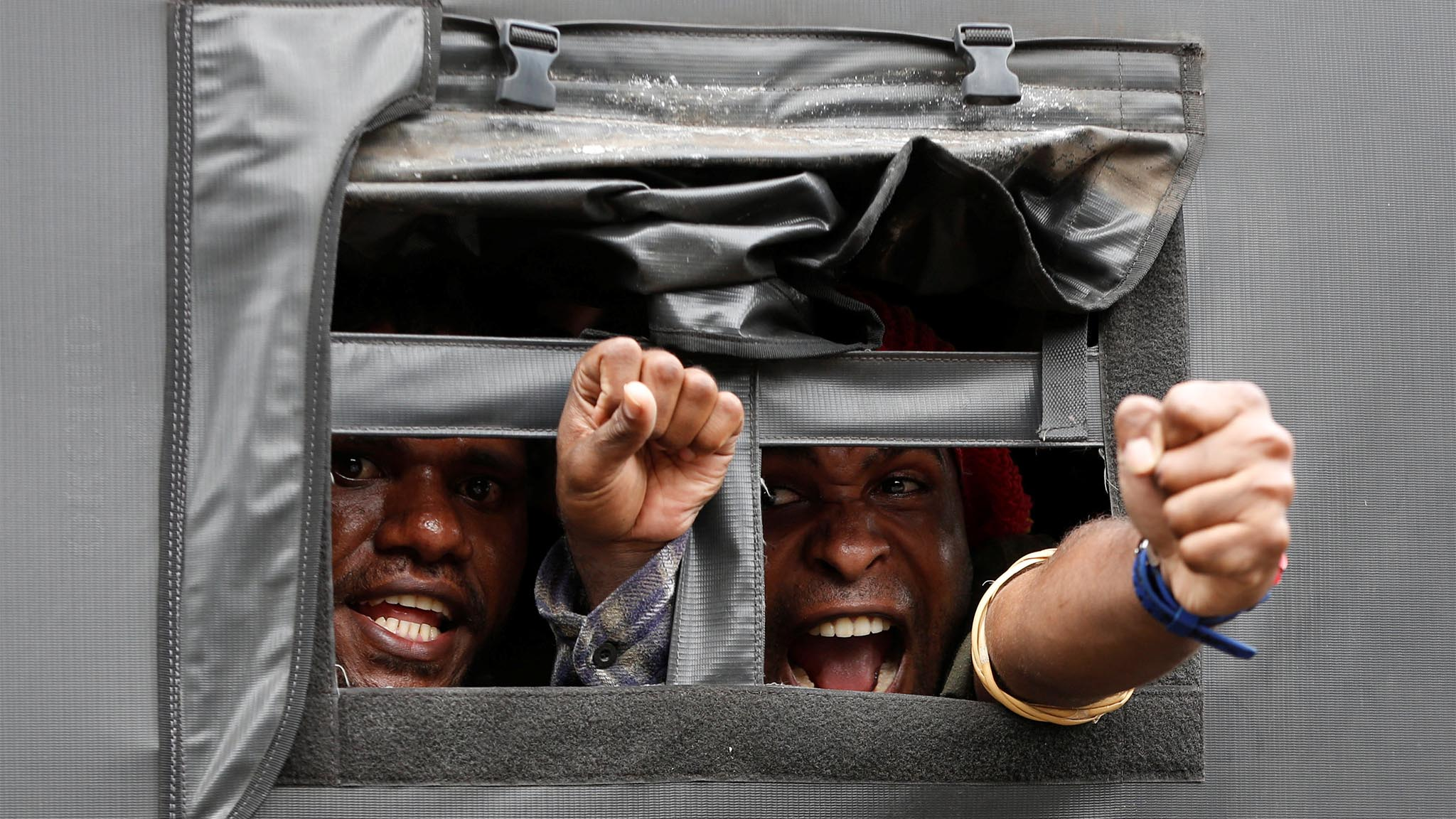 Protesters shout from a police truck following a rally calling for their right to self-determination in the Indonesian controlled part of Papua in Jakarta