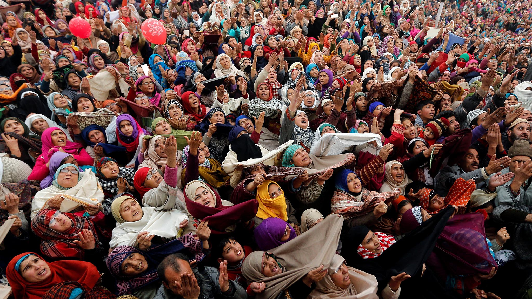Kashmiri Muslims react upon seeing a relic believed to be a hair from the beard of Prophet Mohammed, being displayed on the Friday following the festival of Eid-e-Milad-ul-Nabi, the birthday anniversary of the prophet, at the Hazratbal shrine in Srinagar