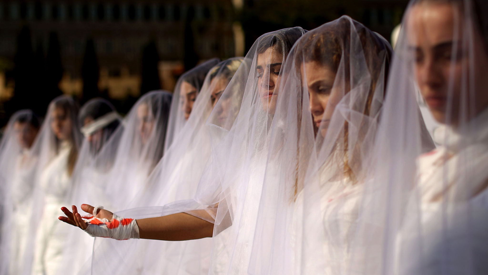 "Activists from the Lebanese NGO Abaad (Dimensions), a resource centre for gender equality, dressed as brides and wearing injury patches hold a protest in downtown Beirut on December 6, 2016, against article 522 in the Lebanese penal code.  The article shields rapists from prosecution on the condition that they marry their victim, a phenomenon that is still practised in the country, especially among conservative families whose chief aim is to preserve the family's so-called ""honour."" / AFP PHOTO / PATRICK BAZPATRICK BAZ/AFP/Getty Images"