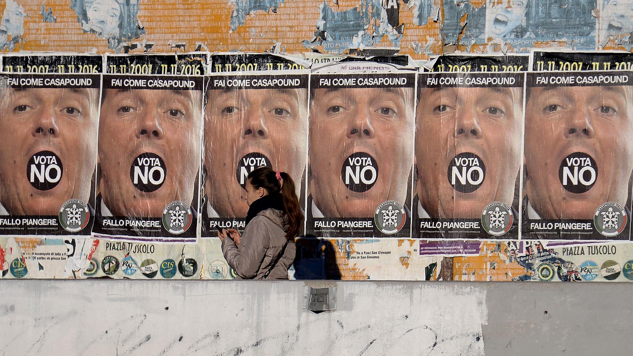 A woman walks past posters from the far-right political movement Casapound