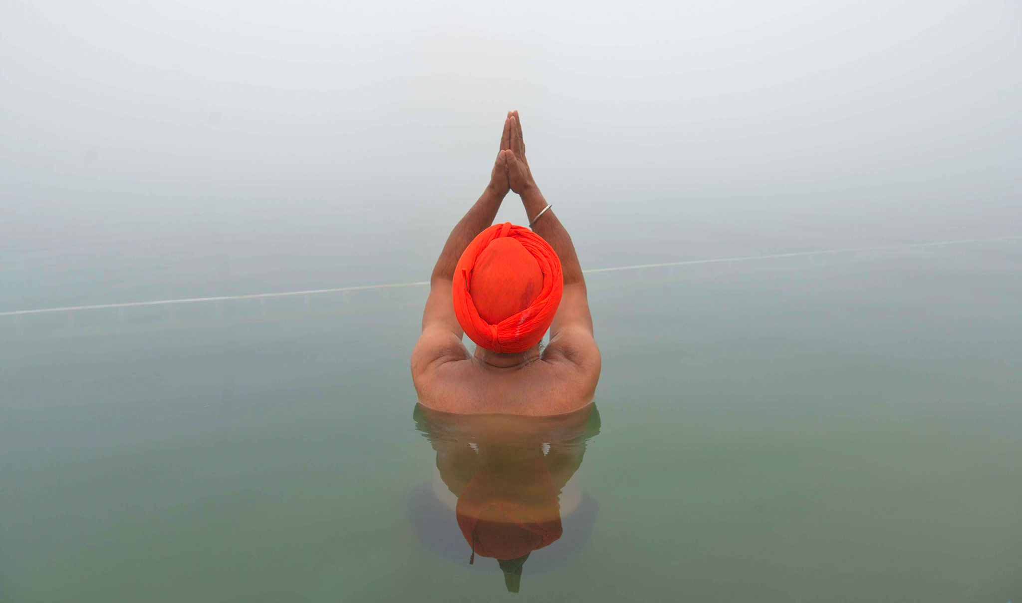 An Indian Sikh devotee takes a dip in the holy sarovar (water tank) during dense fog at the Golden Temple in Amritsar on December 9, 2016. / AFP PHOTO / Narinder NANUNARINDER NANU/AFP/Getty Images