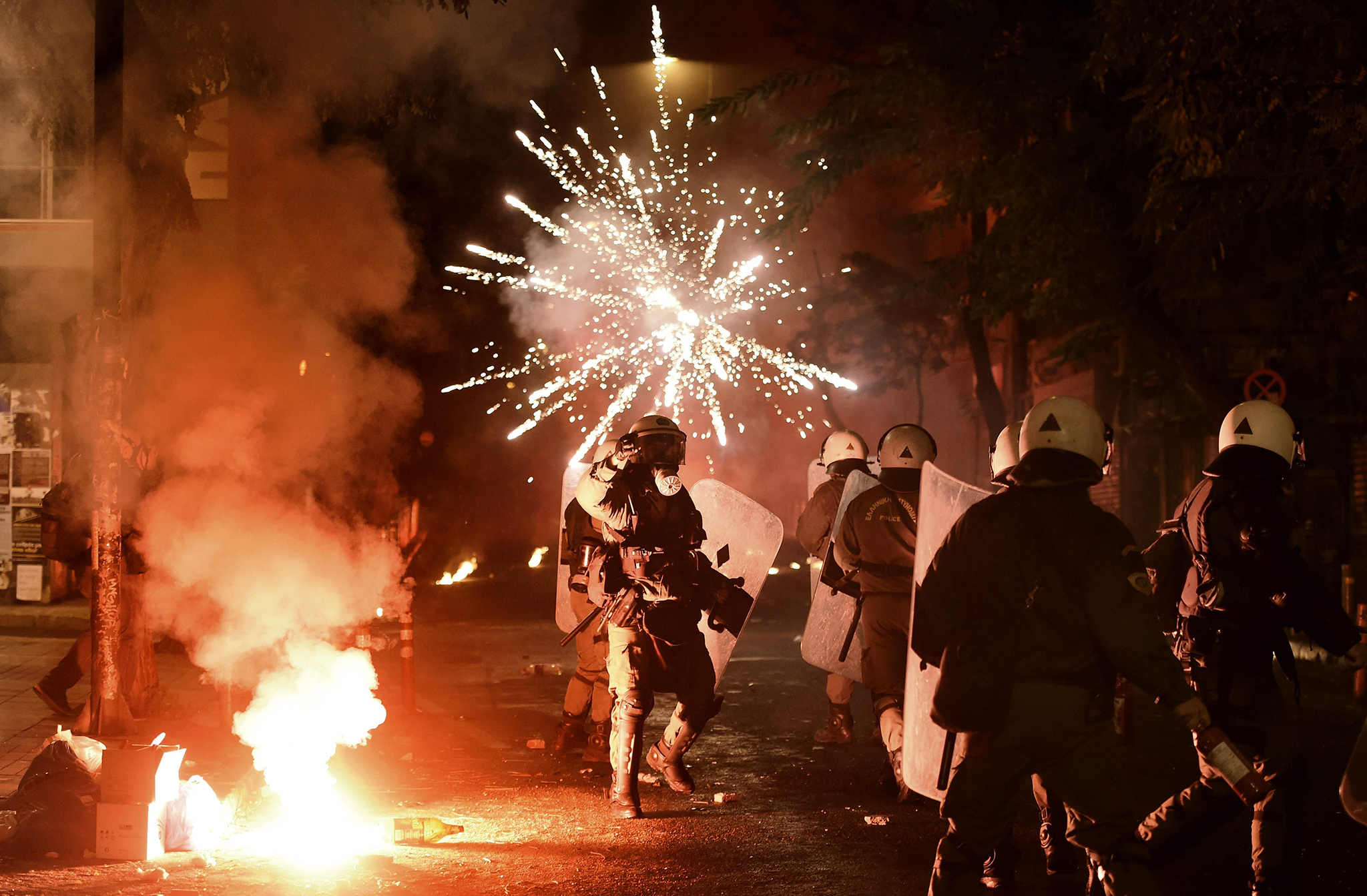 Police officers look on as a firework thrown by protesters explodes in front of them in the central district of Exarchia in Athens, on December 6, 2016, following a commemorative rally marking the eighth anniversary of the killing of teenager Alexandros Grigoropoulos by a Greek police officer.   Hundreds of  pupils, university students and workers  participated in  a  rally to mark the eighth anniversary of the fatal police shooting of a 15-years old student , which sparked riots in the country in 2008.    / AFP PHOTO / ARIS MESSINISARIS MESSINIS/AFP/Getty Images