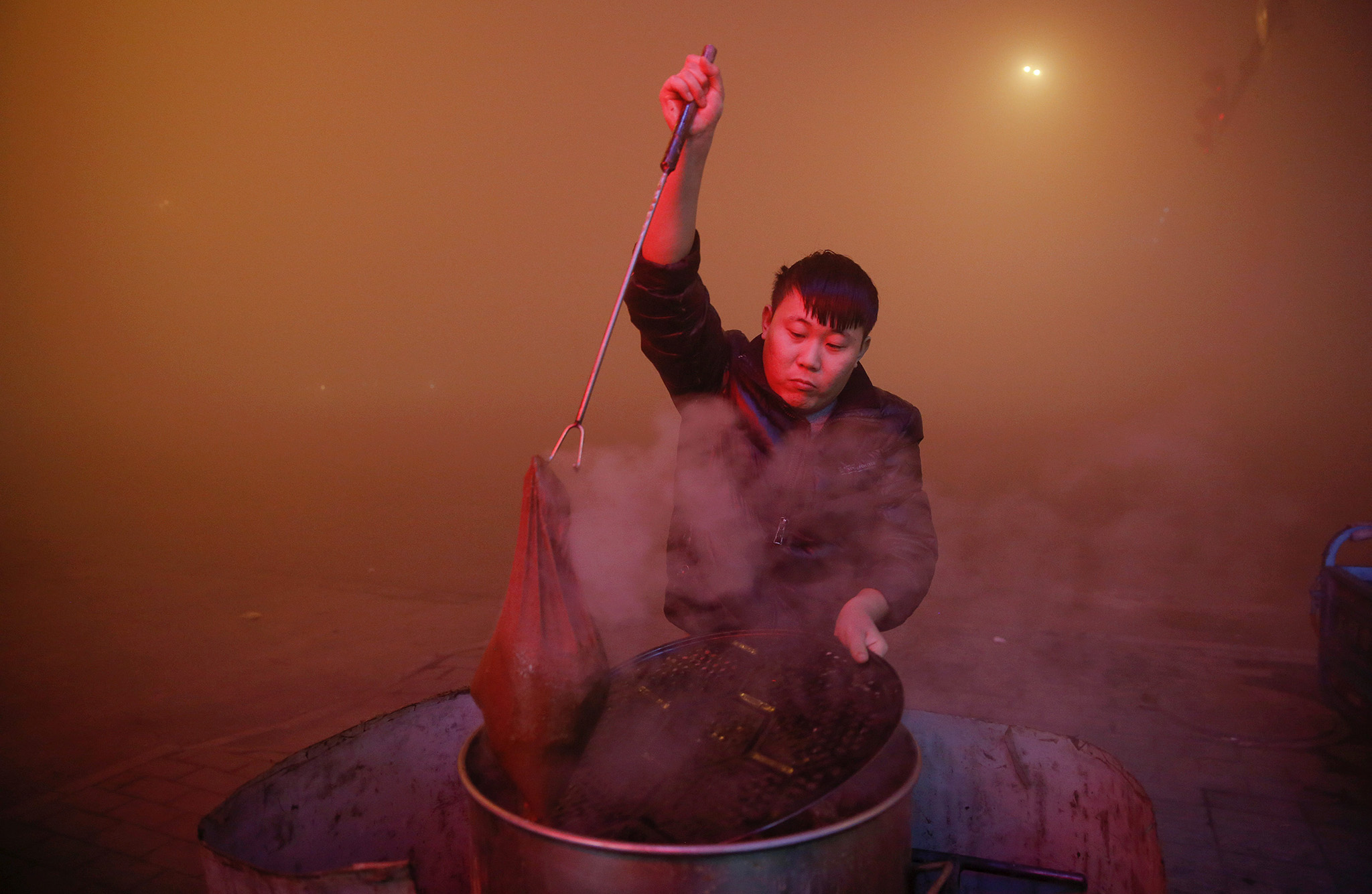 A man cooks in open air as heavy smog blankets Shengfang, in Hebei province, on an extremely polluted day with red alert issued, China December 19, 2016. REUTERS/Damir Sagolj