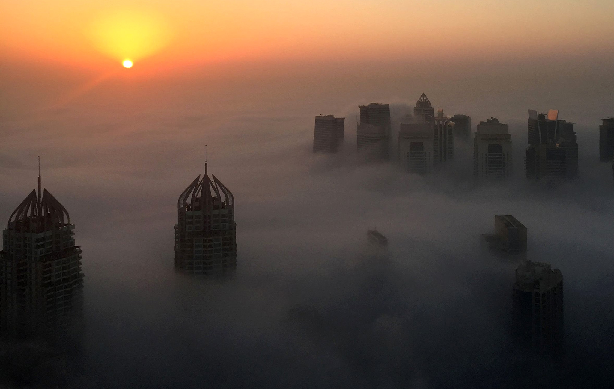 The sun rises behind skyscrapers amidst the clouds on a foggy morning in Dubai on December 5, 2016.