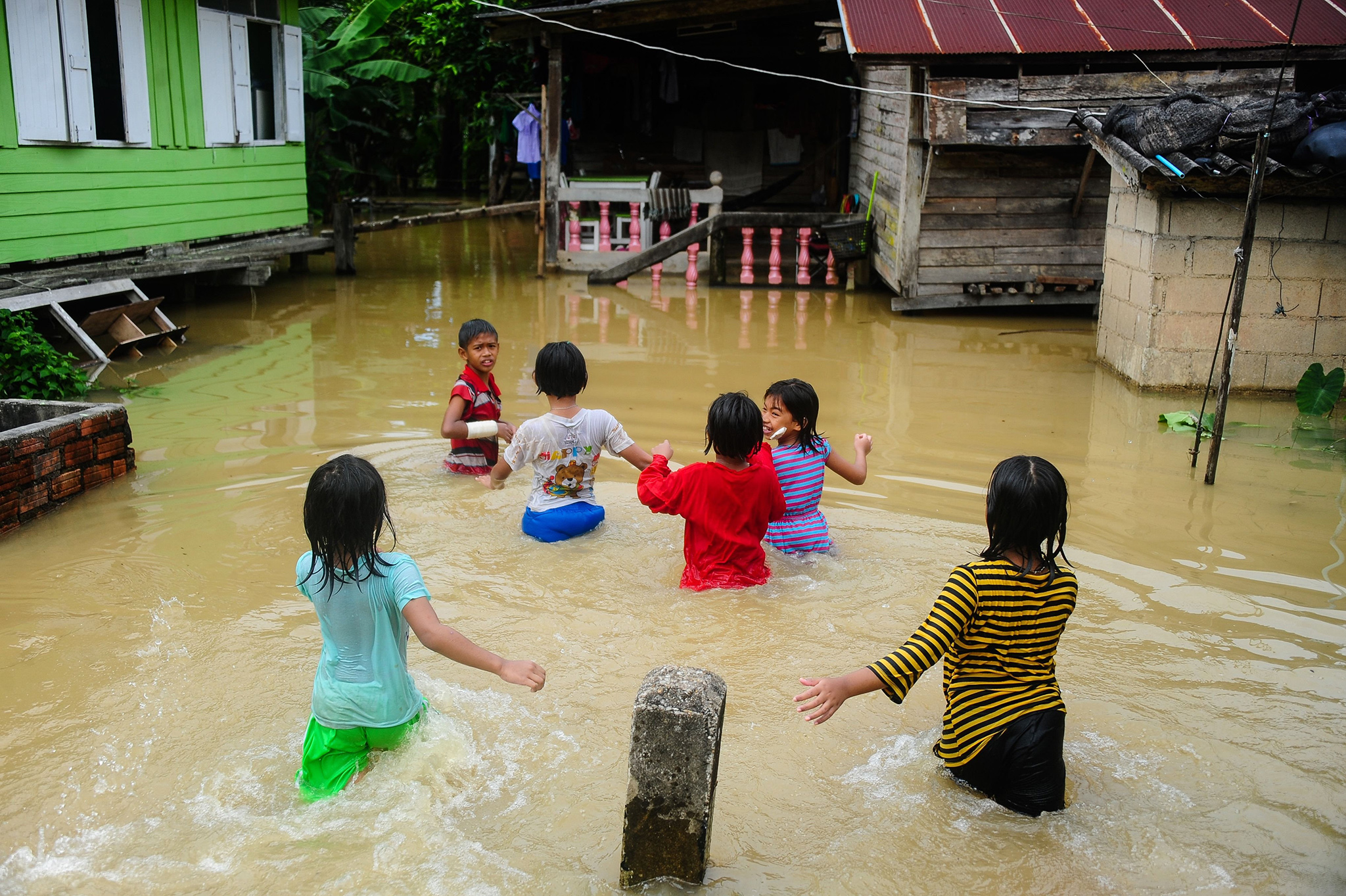 Children play near houses inundated by floodwaters after heavy rains in the Rangae district of the southern province of Narathiwat on December 21, 2016. / AFP PHOTO / MADAREE TOHLALAMADAREE TOHLALA/AFP/Getty Images