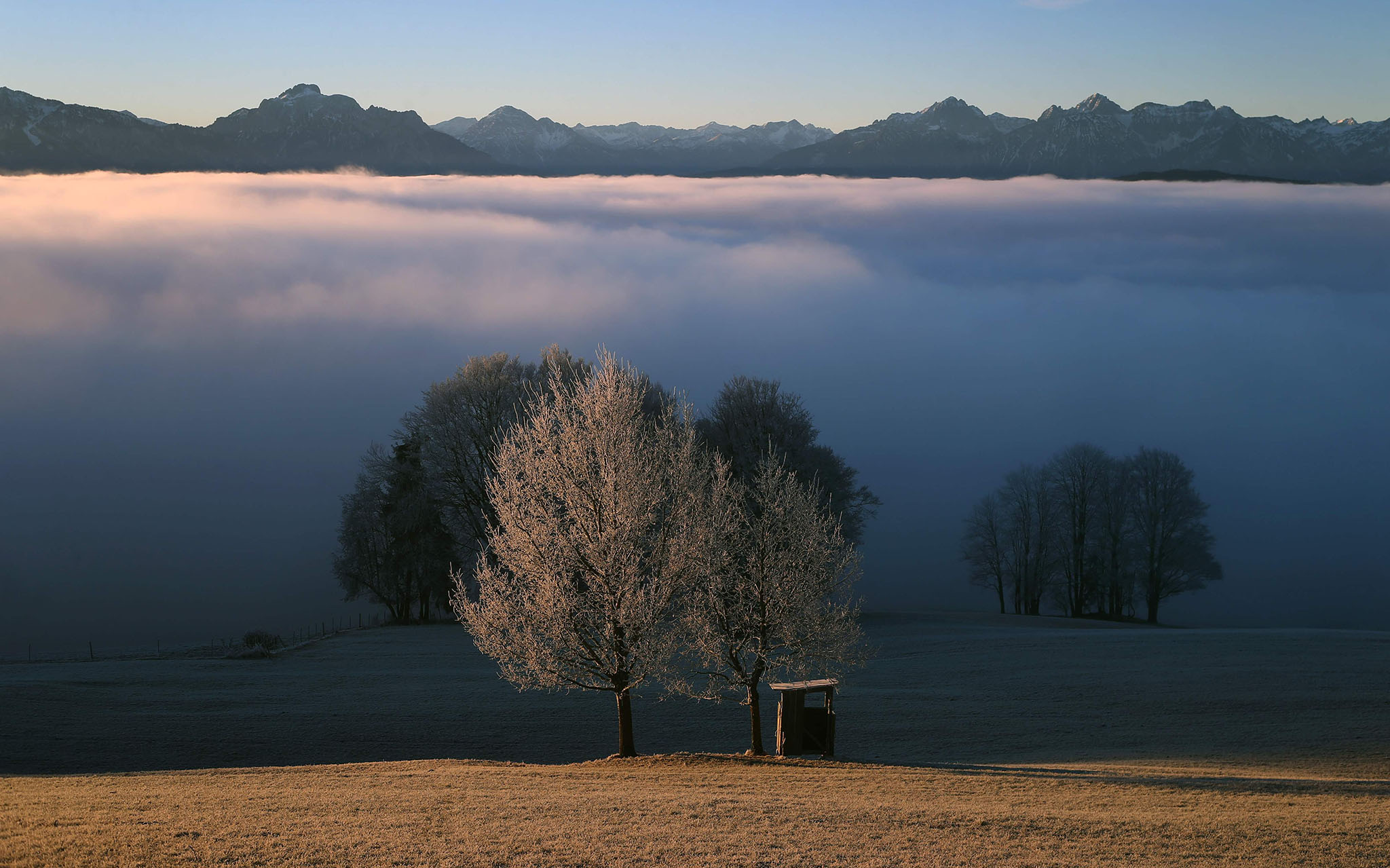 The pre-Alpine region near Bernbeuren, southern Germany, is pictured during the sunrise on December 16, 2016. / AFP PHOTO / dpa / Karl-Josef Hildenbrand / Germany OUTKARL-JOSEF H