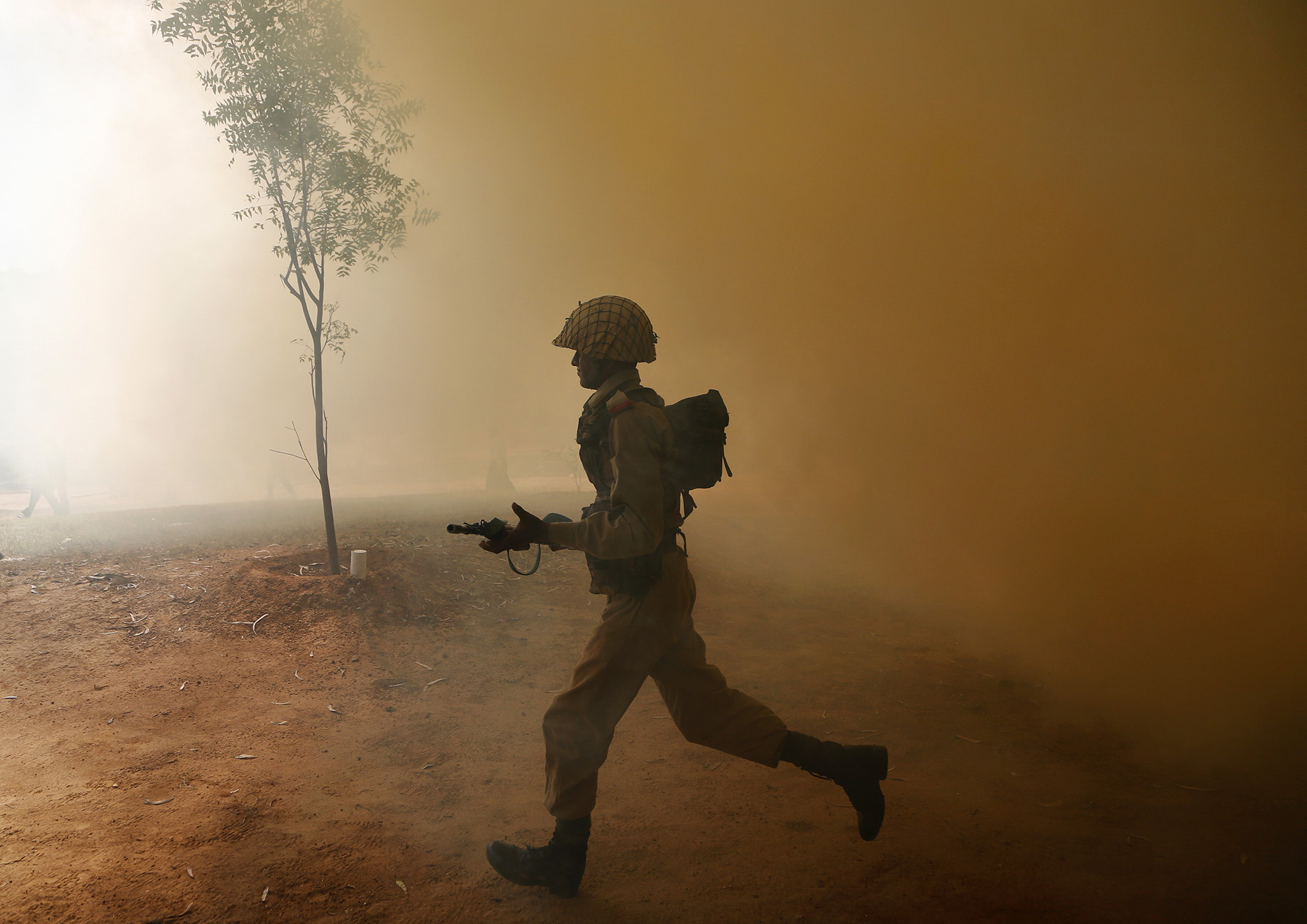 An Indian army soldier runs amid smoke from canisters during a session to showcase skills at the Army Service Corps training centre in Bangalore, India, Monday, Dec. 5, 2016. (AP Photo/Aijaz Rahi)