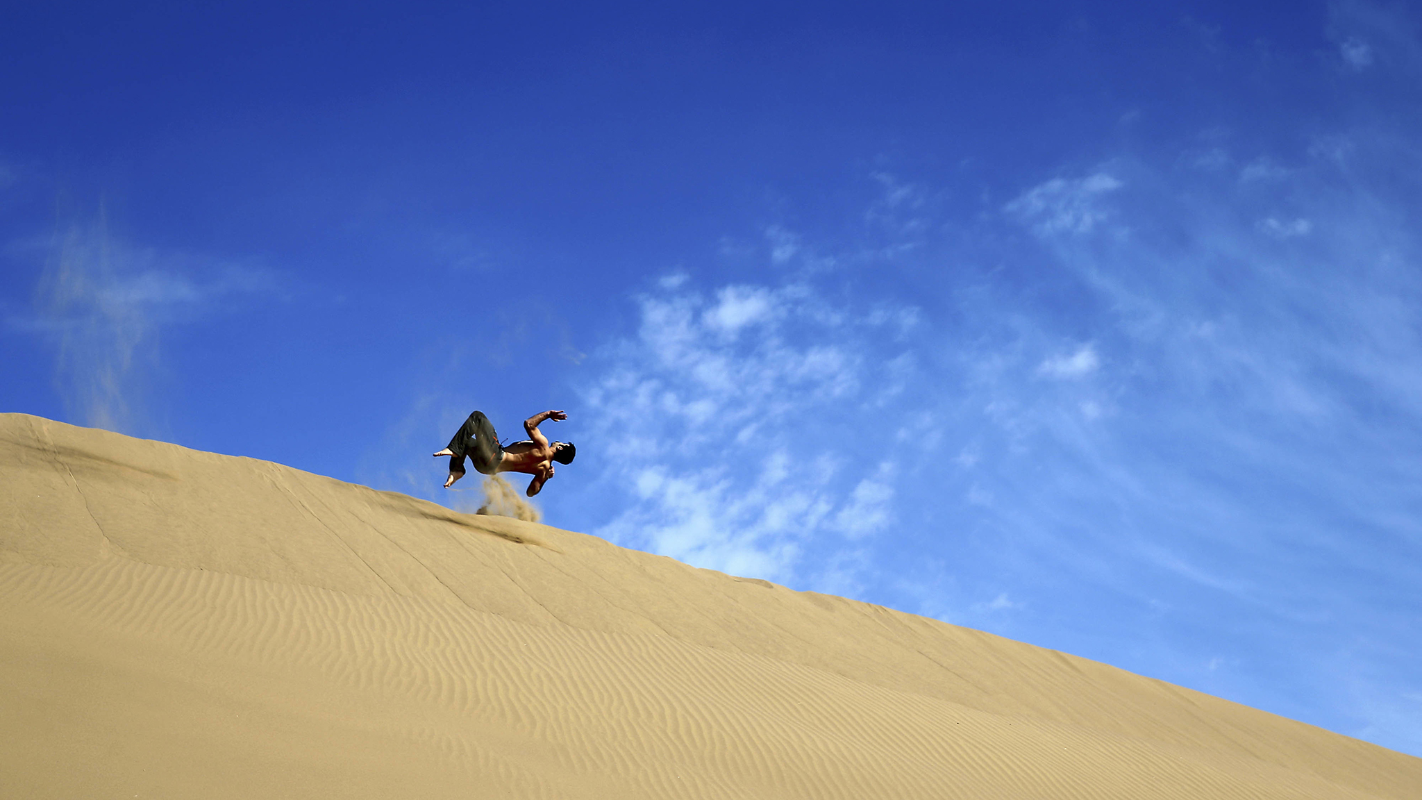 In this picture taken on Thursday, Dec. 1, 2016, an Iranian man flips on the sands while enjoying his weekend in the Mesr desert about 305 miles (500 kilometers) southeast of the capital Tehran, Iran. Deserts make up parts of Iran which have recently become tourist destination for young Iranians looking for a break on their weekend. The increase in tourists to the desert has stimulated economic growth in the area. (AP Photo/Ebrahim Noroozi)