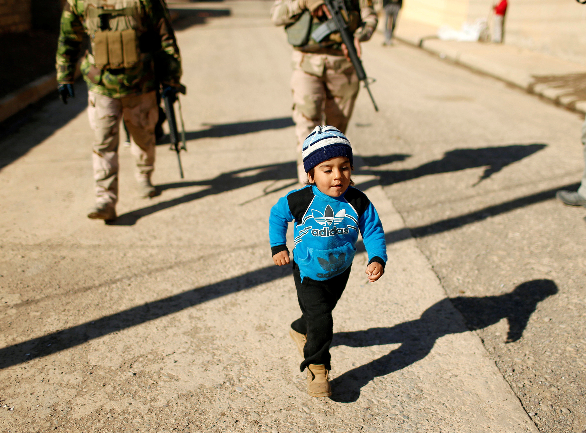 A child walks in front of Iraqi army during an operation against Islamic State militants in the neighbourhood of Intisar, eastern Mosul, Iraq, December 6, 2016. REUTERS/Ahmed Jadallah