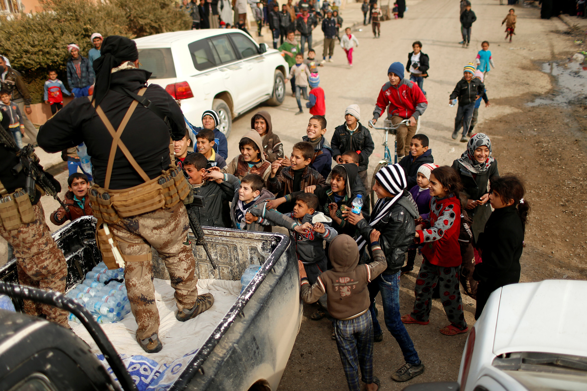 Iraqi soldiers distribute water to children outside a distribution point run by United Nations agencies at Zahra district, east of Mosul, Iraq December 8, 2016. REUTERS/Ahmed Jadallah.