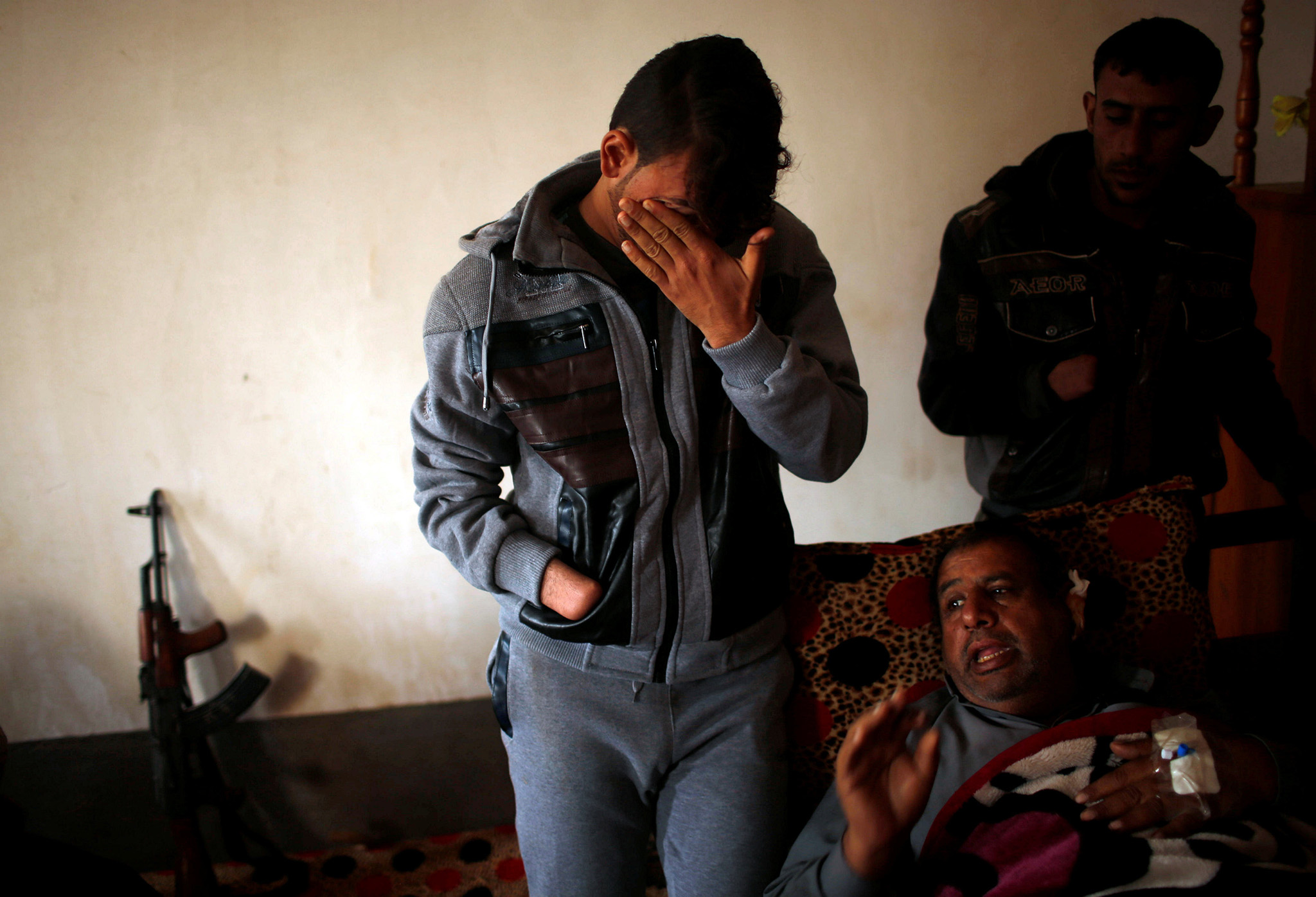 Azad Hassan (L), whose hand was chopped off by Islamic State militants, cries as he stands beside his wounded father in a house at Nimrud village, south of Mosul, Iraq, December 13, 2016. Picture taken December 13, 2016. REUTERS/Mohammed Salem