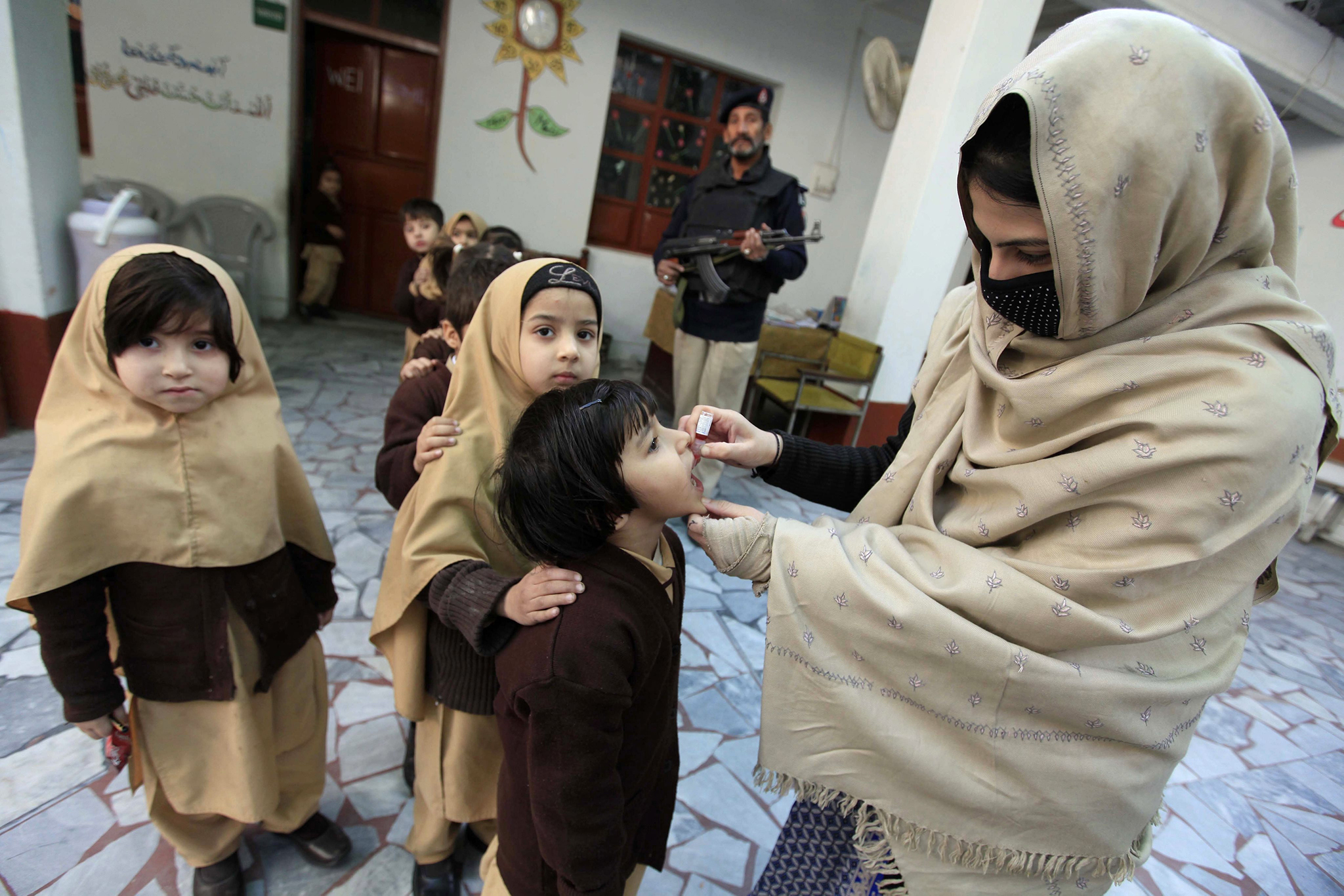 epa05684220 A soldier guards polio vaccination team administering polio vaccination to children during a three-day countrywide vaccination campaign in Peshawar, Pakistan, 21 December 2016. Pakistan is one of the last two countries, along with Afghanistan, where polio is still endemic. Though new polio cases dropped to a nine-year low in 2016, attacks by Islamist militants against health workers and police guarding them remained a challenge for a UN-funded vaccination campaign.  EPA/ARSHAD ARBAB