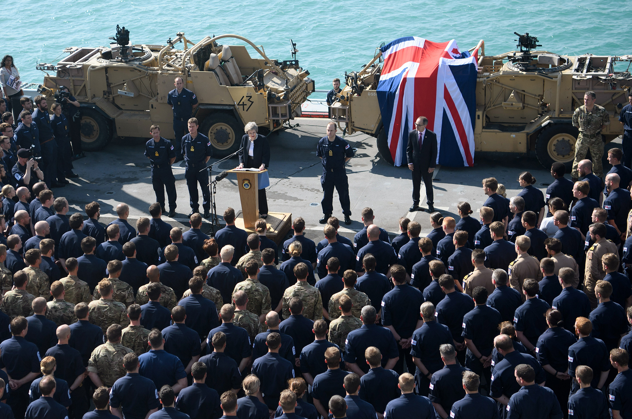 British Prime Minister Theresa May addresses sailors on board HMS Ocean during her trip to attend the Gulf Cooperation Council summit in Bahrain, on December 6, 2016 in Manama, Bahrain. Prime Minister May is the first British leader and the first woman to attend the annual two-day Gulf Cooperation Council and will attend a dinner with the leaders of Saudi Arabia, Kuwait, the United Arab Emirates, Qatar, Bahrain and Oman on Tuesday, and will also discuss the situation in Yemen and Syria.  (Photo by Carl Court/Getty Images)
