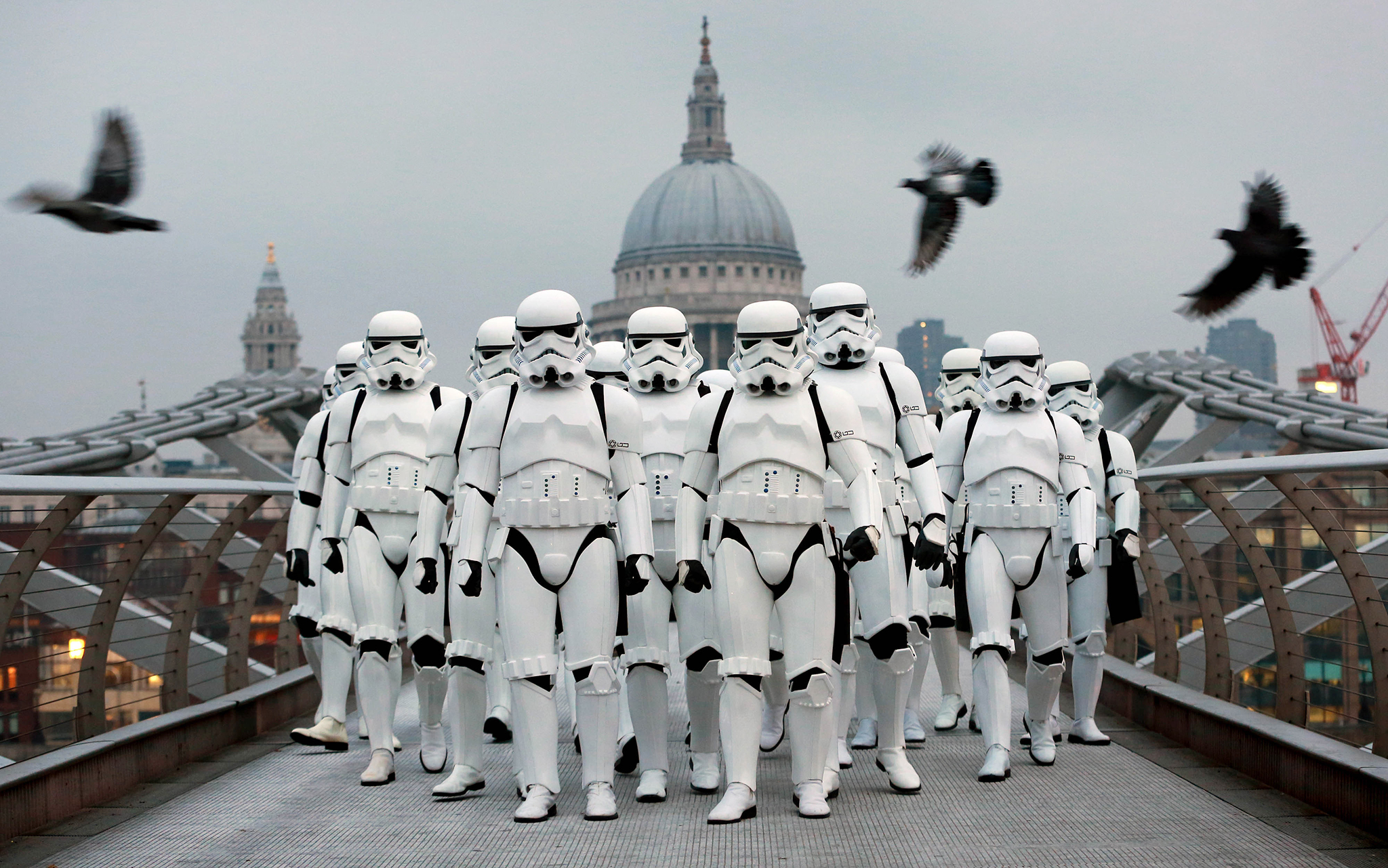 A group of Star Wars fans dressed as Stormtroopers walk across Millennium Bridge in London, to celebrate the launch of Rogue One: A Star Wars Story, which is released nationwide today. PRESS ASSOCIATION Photo. Picture date: Thursday December 15, 2016. Photo credit should read: Matt Alexander/PA Wire