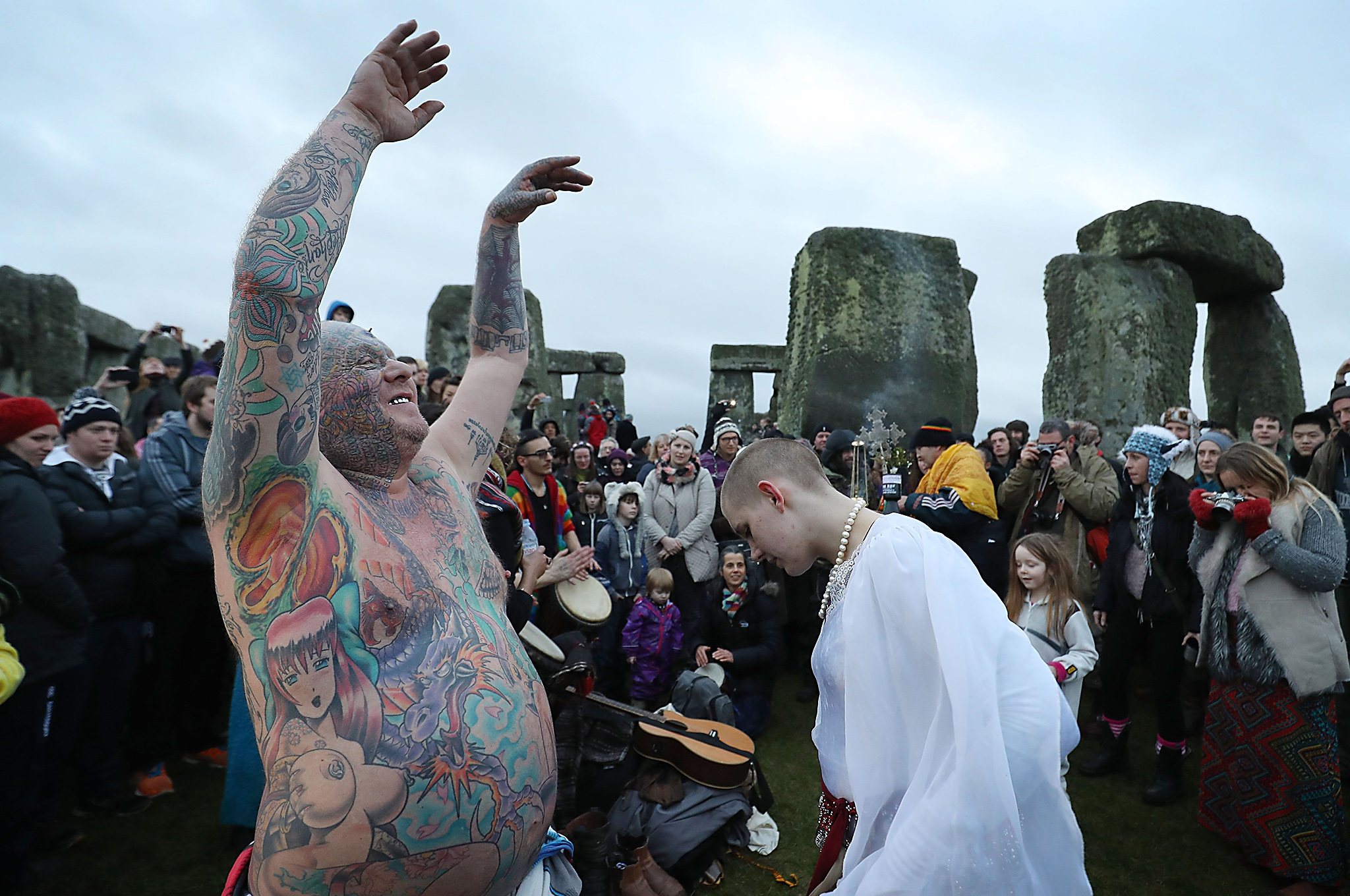 Druids, pagans and revellers gather in the centre of Stonehenge as they take part in a winter solstice ceremony at the ancient neolithic monument of Stonehenge near Amesbury on December 21, 2016 in Wiltshire, England. Despite a forecast for cloud and rain, a large crowd gathered at the famous historic stone circle, a UNESCO listed ancient monument, to celebrate the sunrise closest to the Winter Solstice, the shortest day of the year. The event is claimed to be more important in the pagan calendar than the summer solstice, because it marks the 're-birth' of the Sun for the New Year.  (Photo by Matt Cardy/Getty Images)
