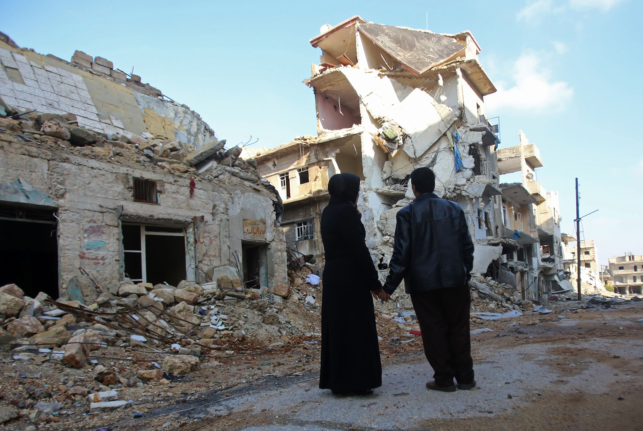 Kefa Jawish (L) and her husband Tajeddin Ahmed look a destroyed building in the Aleppo's northeastern Haydariya neighbourhood as they head to check their house for the first time in four years on December 4, 2016.    Jawish was among hundreds of Syrians returning to east Aleppo in recent days after the army recaptured large swathes of the city from rebels and encouraged residents to visit neighbourhoods and homes they left years earlier.   / AFP PHOTO / Youssef KARWASHAN / TO GO WITH AFP STORY BY RIM HADDADYOUSSEF KARWASHAN/AFP/Getty Images