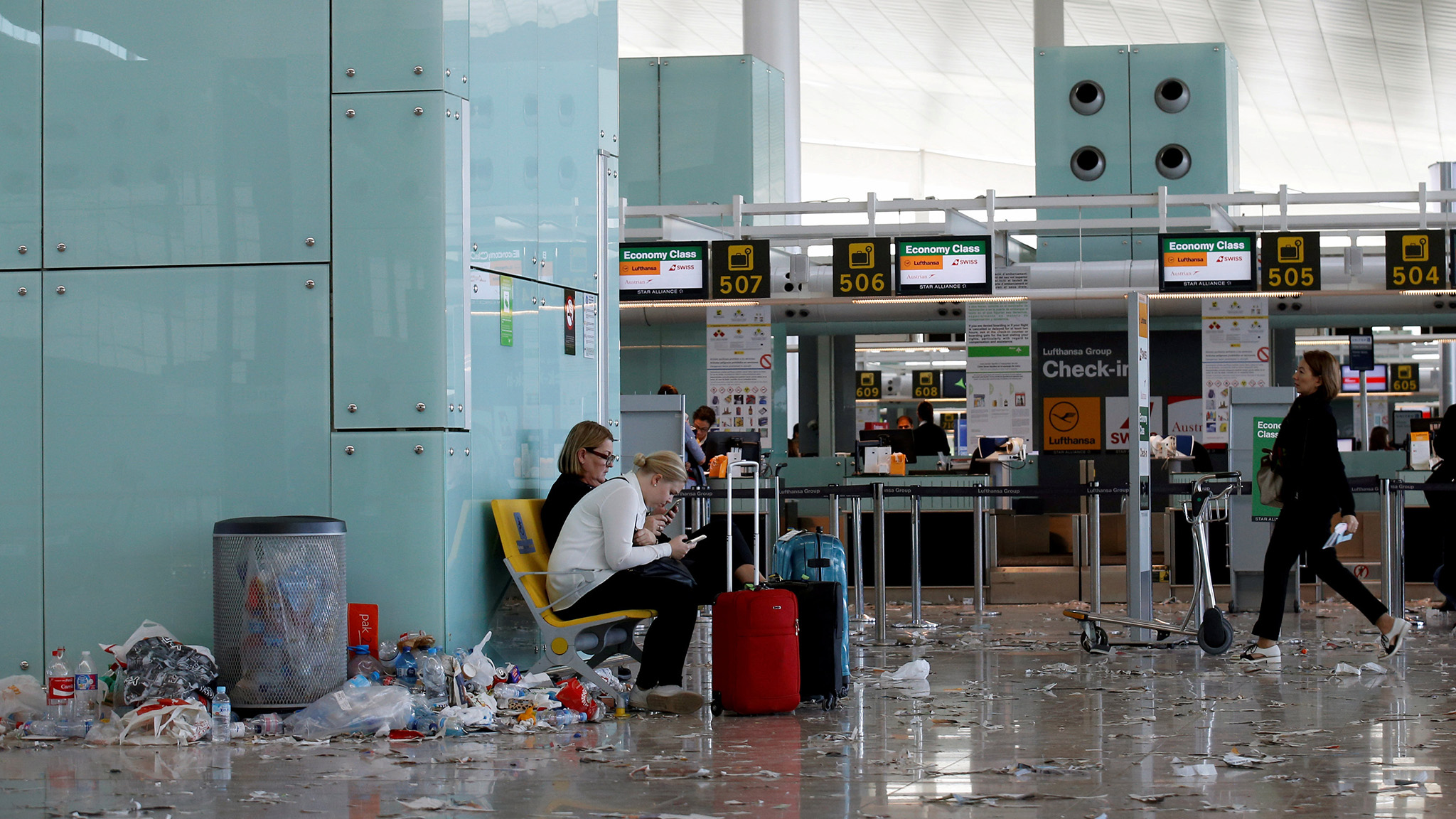 Passengers check their mobiles as garbage is accumulated during a protest by the cleaning staff at Barcelona's airport