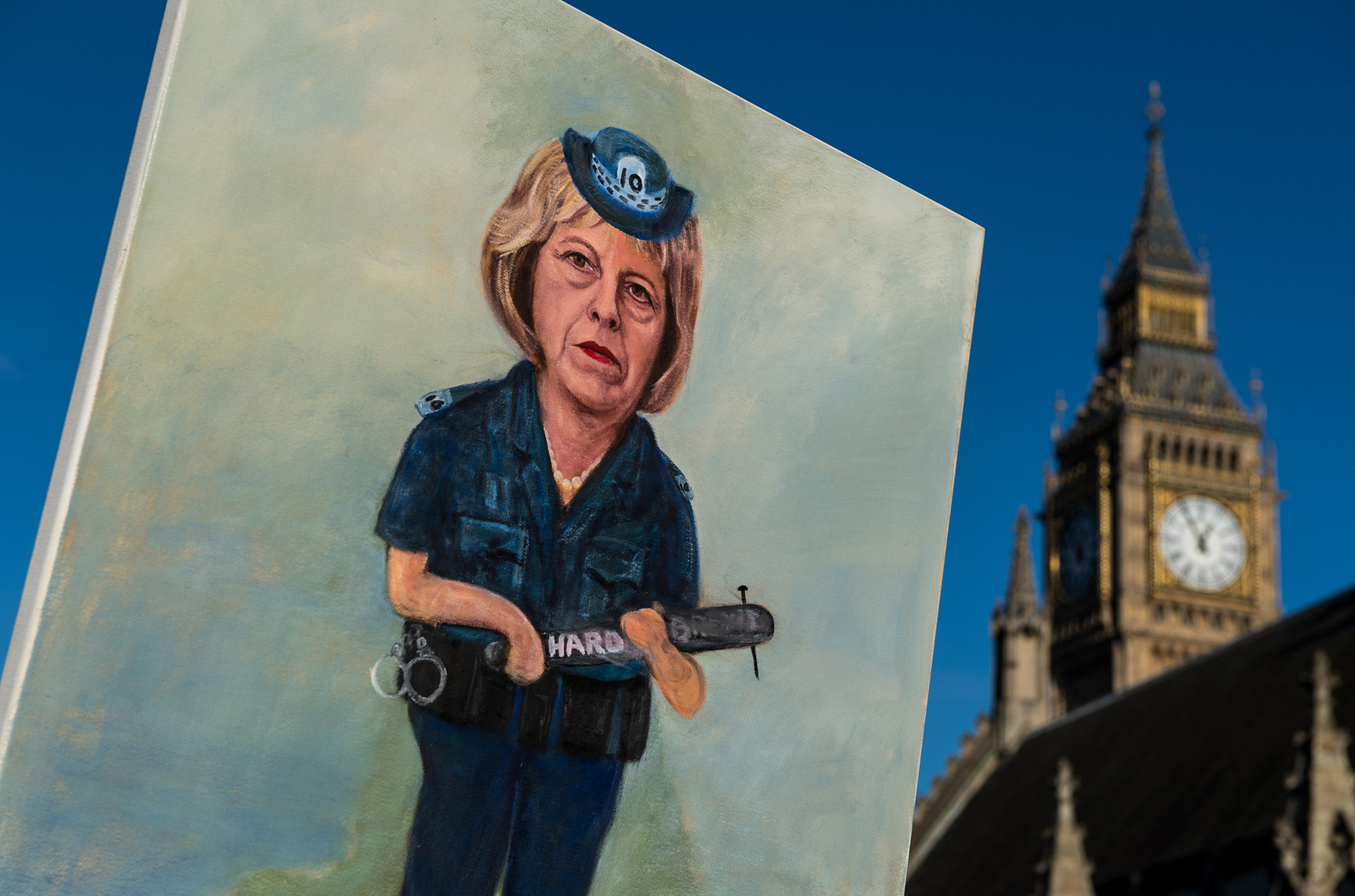 Artist Kaya Mar holds his latest painting of Theresa May dressed as a police officer holding a truncheon with 'Hard Brexit' written on it in front of the Houses of Parliament on January 17, 2017 in London, England. Today in a long awaited speech, British Prime Minister Theresa May outlined the prioirites for the United Kingdom in Brexit negotiations.  (Photo by Chris J Ratcliffe/Getty Images)