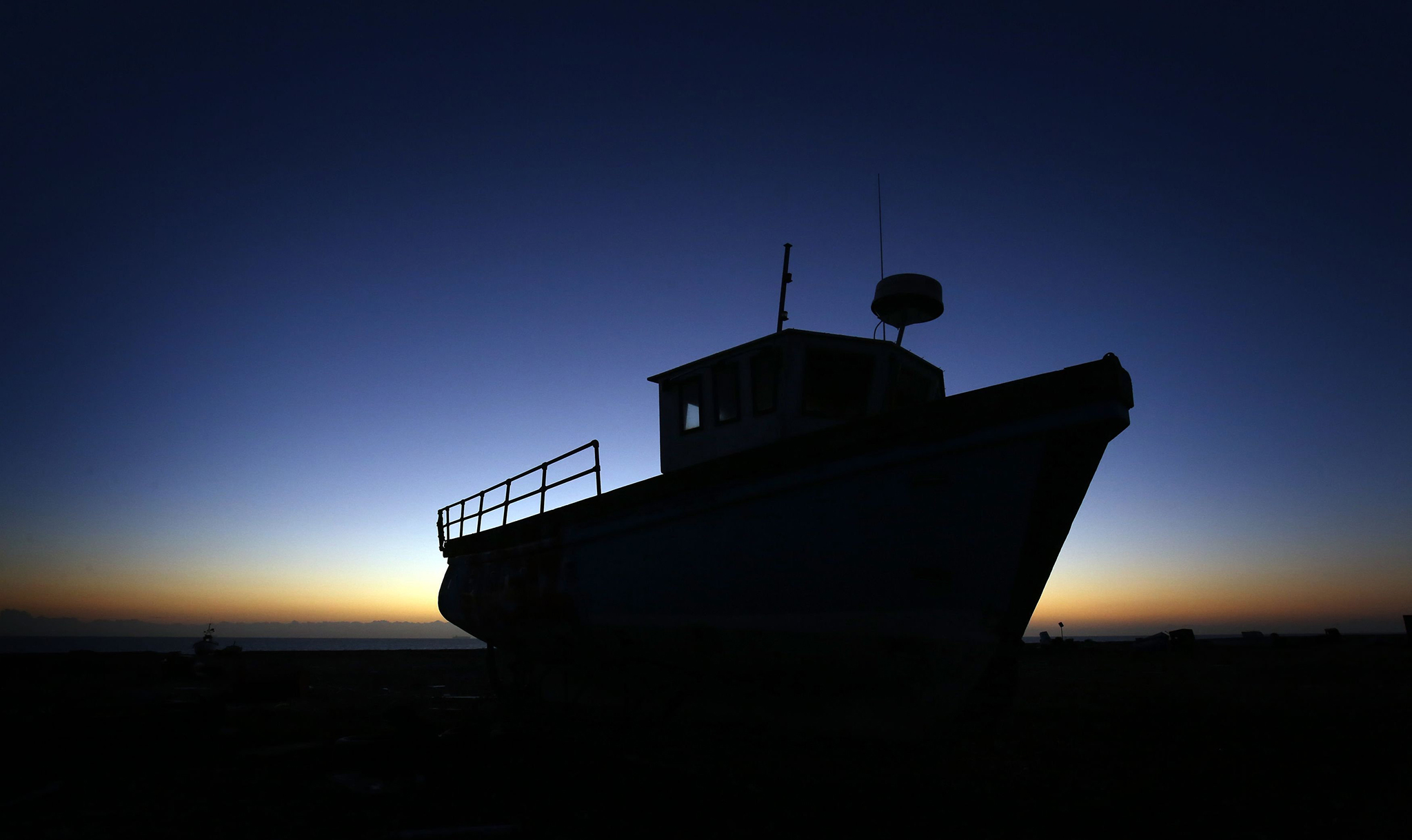 The sun rises behind a fishing boat on the beach in Dungeness, Kent. PRESS ASSOCIATION Photo. Picture date: Thursday January 5, 2017. See PA story WEATHER Cold. Photo credit should read: Gareth Fuller/PA Wire