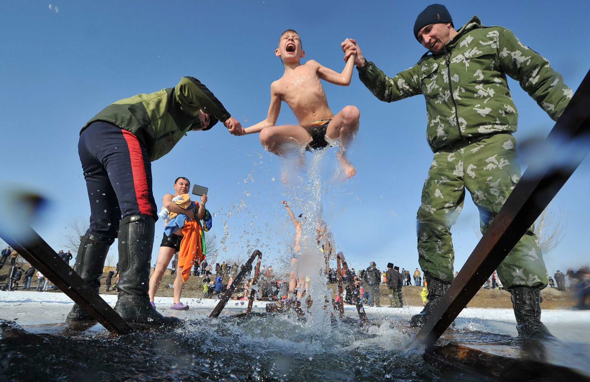 Cossacks help a boy to take a bath in the icy waters of a lake during the celebration of the Epiphany holiday near the village of Leninskoe, some 15 km of Bishkek, on January 19, 2017. / AFP PHOTO / Vyacheslav OSELEDKOVYACHESLAV OSELEDKO/AFP/Getty Images