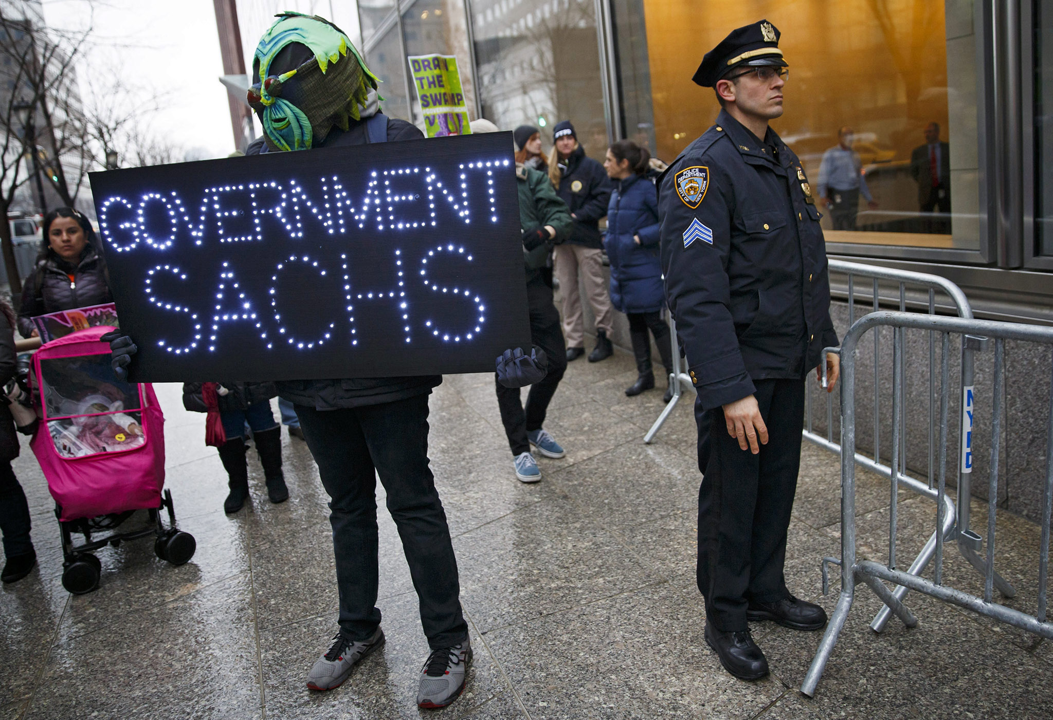 A man holds a sign while standing next to a place officer in front of the offices of the financial firm Goldman Sachs during a protest against the company's involvement and influence with the incoming Trump administration in New York, New York, USA, 17 January 2017. The group was planning on camping out in front of the company's offices until 20 January when US President-elect Trump is scheduled to be sworn in as the next US President.  EPA/JUSTIN LANE