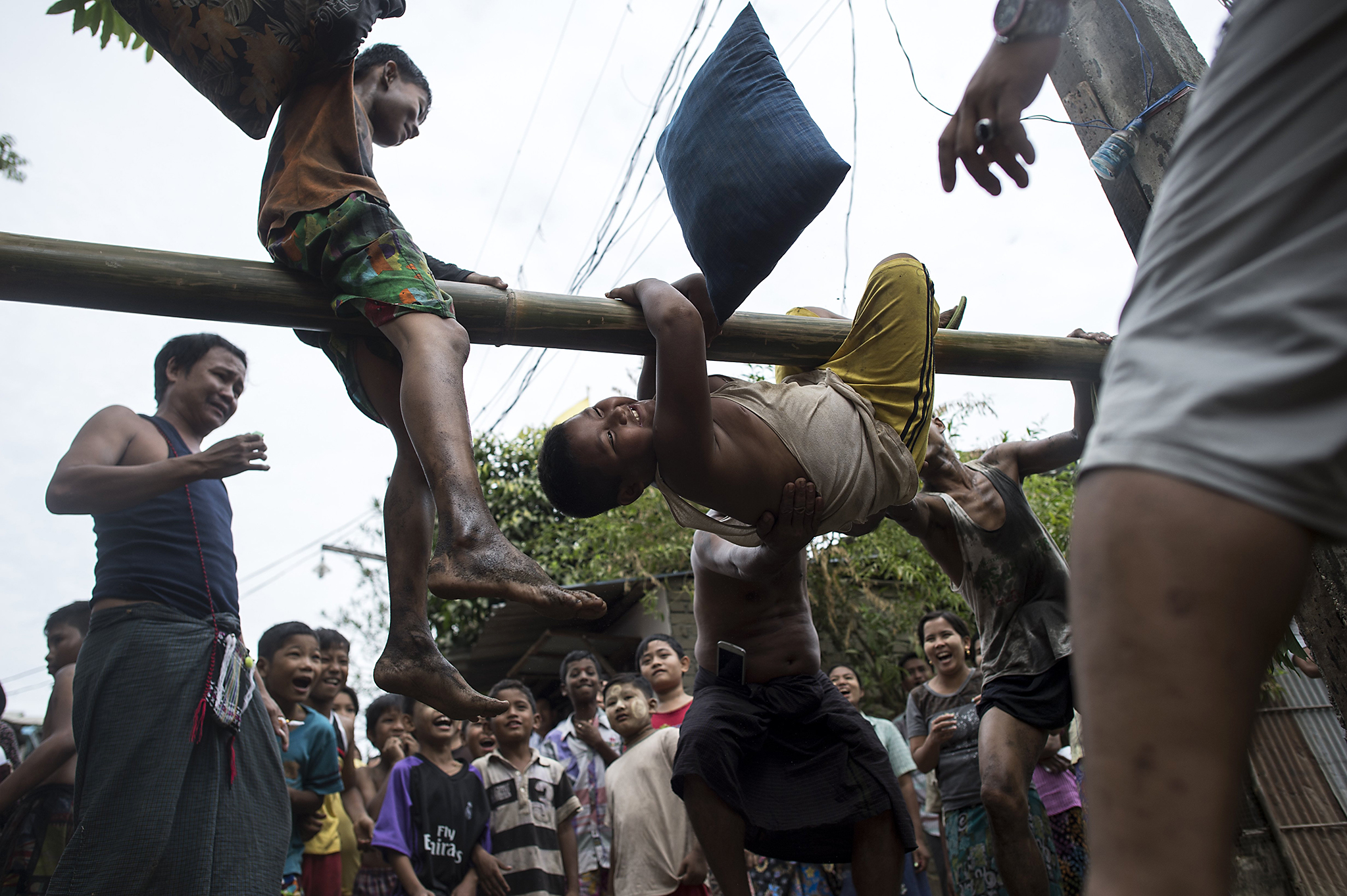 Youths play a traditional pillow fight game on a bamboo pole during festivities marking the 69th anniversary of Myanmar Independence Day on the outskirts of Yangon on January 4, 2017.  Various traditional and local events were held on the holiday which marks the 69th anniversary of the country known before as Burma when British colonial rule ended on January 4, 1948. / AFP PHOTO / YE AUNG THUYE AUNG THU/AFP/Getty Images