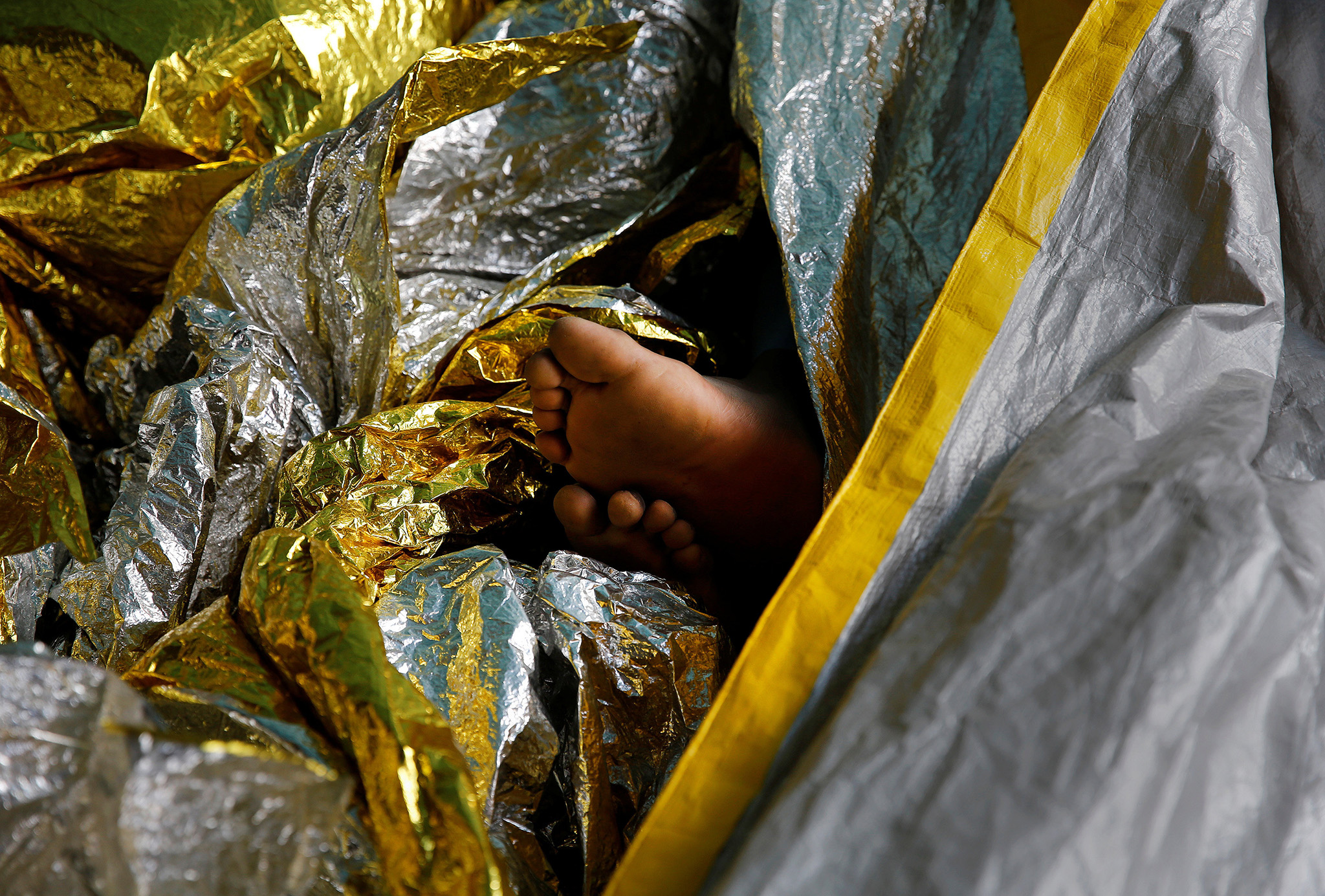 A migrant's feet peeks out of thermal blankets onboard the former fishing trawler Golfo Azzurro after being rescued along with other migrants, including children and pregnant women, by the Spanish NGO Proactiva Open Arms from a raft that drifted out of control in the central Mediterranean Sea, some 36 nautical miles off the Libyan coast, January 3, 2017. REUTERS/Yannis Behrakis