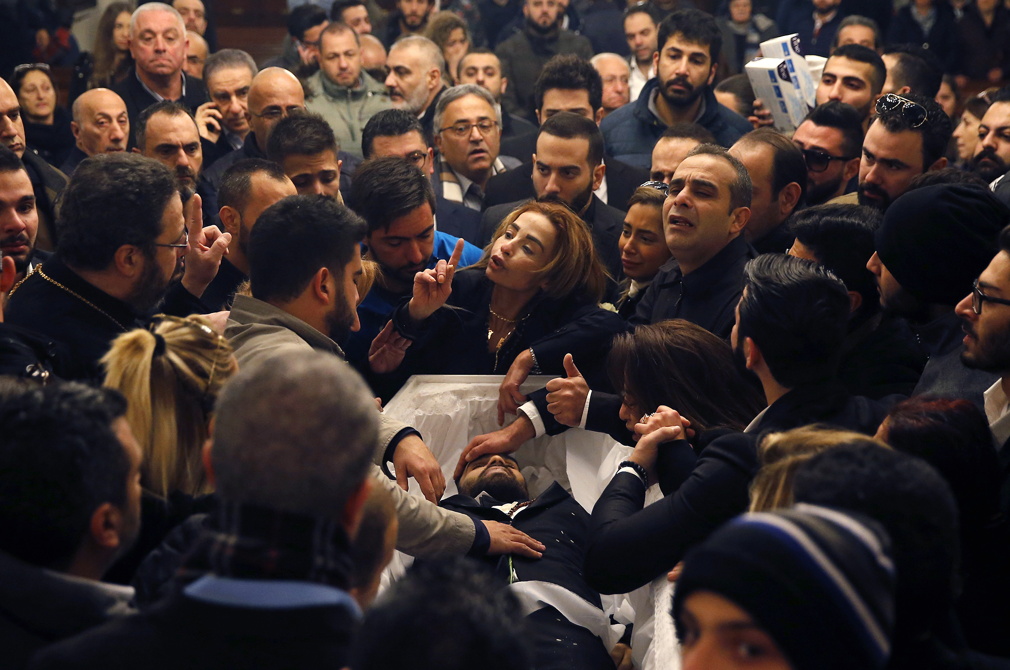 "The sister of Elias Wardini, center, a Lebanese man who was killed in the New Year's Eve Istanbul nightclub attack, mourns over her brother's body during his funeral procession at a church, in Beirut, Lebanon, Tuesday, Jan. 3, 2017. The gunman killed 39 people, most of them foreigners, including three Lebanese citizens, at the Istanbul nightclub. The Islamic State group claimed the attack on Monday, saying a ""soldier of the caliphate"" had carried out the mass shooting in response to Turkish military operations against IS in northern Syria. (AP Photo/Hussein Malla)"