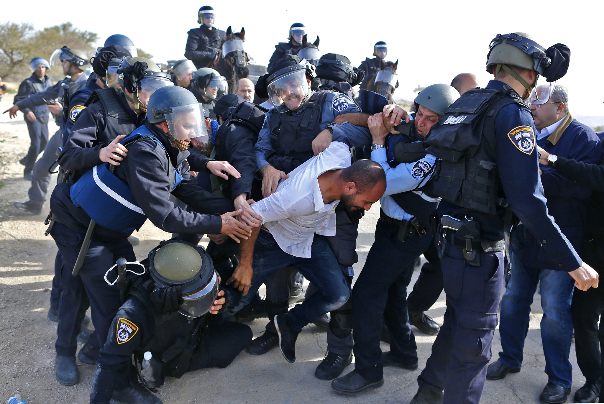 Israeli policemen detain a Bedouin man during clashes that followed a protest against home demolitions on January 18, 2017 in the Bedouin village of Umm al-Hiran, which is not recognized by the Israeli government, near the southern city of Beersheba, in the Negev desert. An Israeli policeman was killed while taking part in an operation to demolish homes in the Bedouin village, with authorities claiming he was targeted in a car-ramming attack. The driver was earlier reported shot dead by police as residents disputed the police version of events, saying the driver was heading to the scene to talk with authorities in an attempt to halt the demolitions. / AFP PHOTO / AHMAD GHARABLIAHMAD GHARABLI/AFP/Getty Images