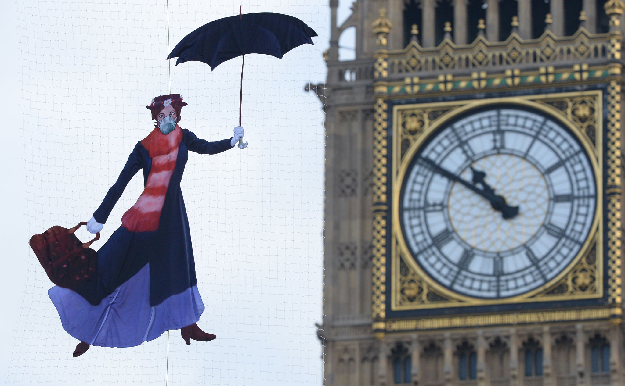 A drawing of Mary Poppins wearing a pollution mask is suspended in front of the Queen Elizabeth Tower at the Palace of Westminster by Greenpeace campaigners after it was revealed that legal air pollution limits for the whole year have been broken just five days into 2017. PRESS ASSOCIATION Photo. Picture date: Friday January 6, 2017. See PA story ENVIRONMENT Pollution. Photo credit should read: Victoria Jones/PA