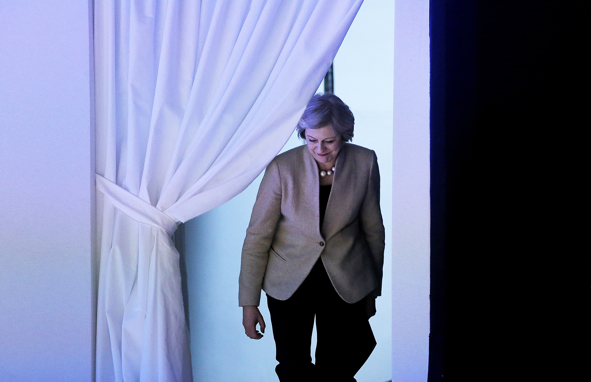 British Prime Minister Theresa May enters the room through a curtain to speak on the third day of the annual meeting of the World Economic Forum in Davos, Switzerland, Thursday, Jan. 19, 2017.  (AP Photo/Michel Euler)