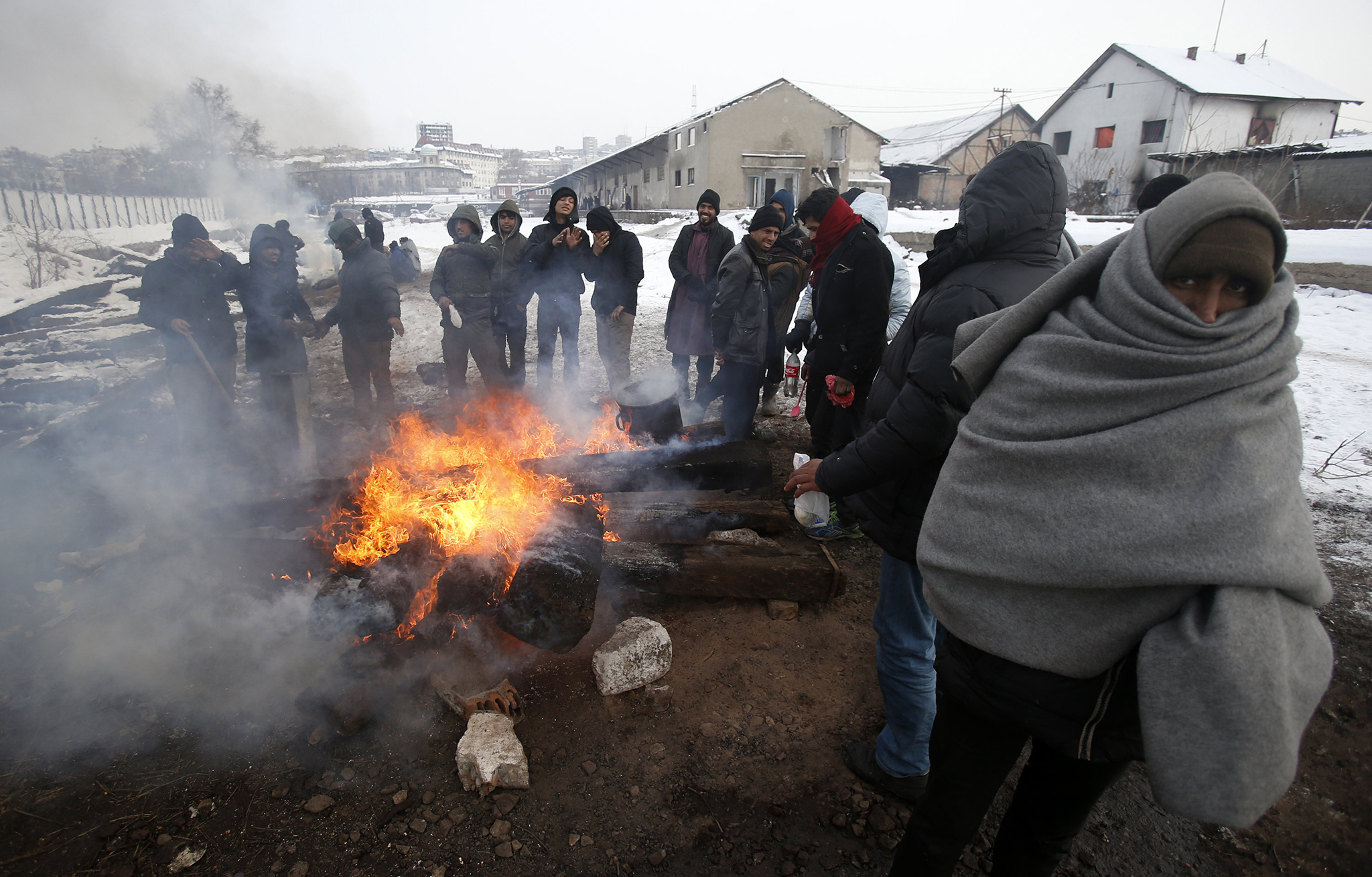 Migrants warm themselves by the fire in front of an abandoned warehouse in Belgrade, Serbia, Tuesday, Jan. 10, 2017. Hundreds of migrants are sleeping rough in parks and make-shift shelters in the Serbian capital in freezing temperatures waiting for a chance to move forward toward the European Union. (AP Photo/Darko Vojinovic)