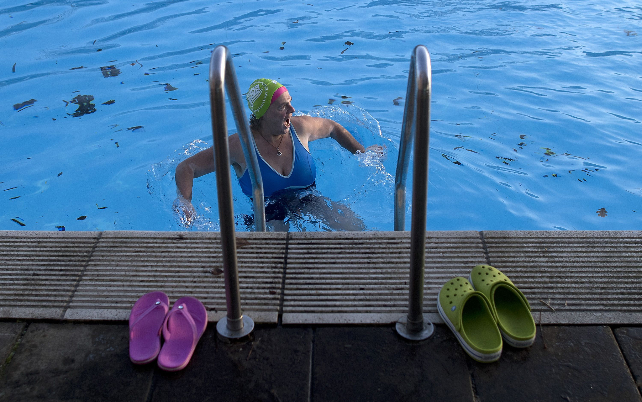 A swimmer reacts after getting into the ice cold water at Tooting Bec Lido, in south west London on January 5, 2017, at sunrise on a freezing winter morning