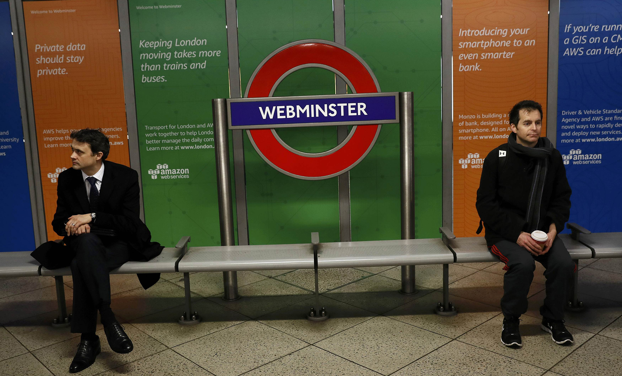Commuter sit next to a tube sign reading 'Webminster' after Amazon rebranded Westminster tube station as a marketing stunt in central London, Britain January 12, 2017. REUTERS/Stefan Wermuth