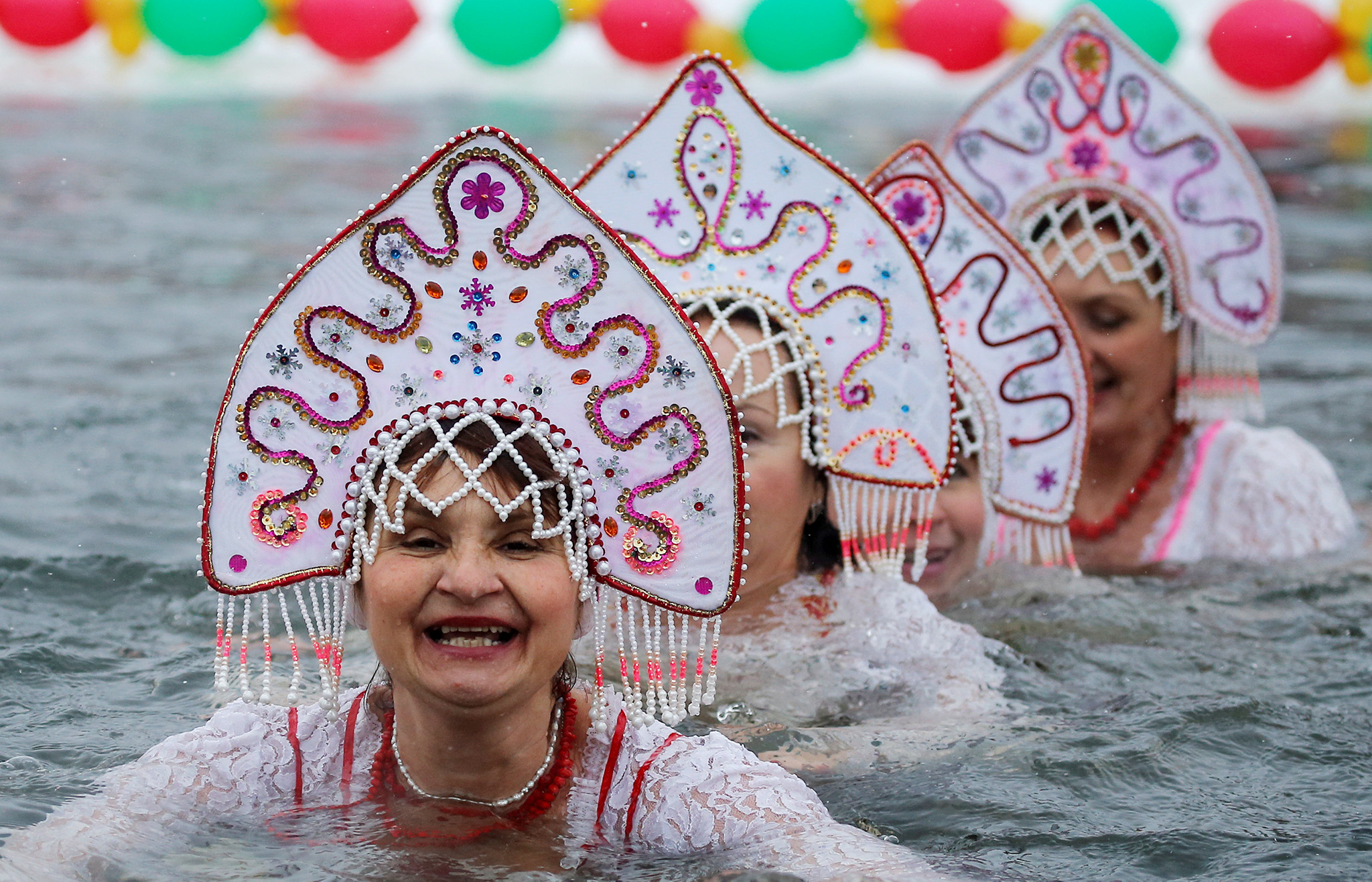 Participants wearing Kokoshnik, the Russian traditional headwear, perform during winter swimming festival in the town of Podolsk, south of Moscow, Russia January 5, 2017. REUTERS/Maxim Shemetov