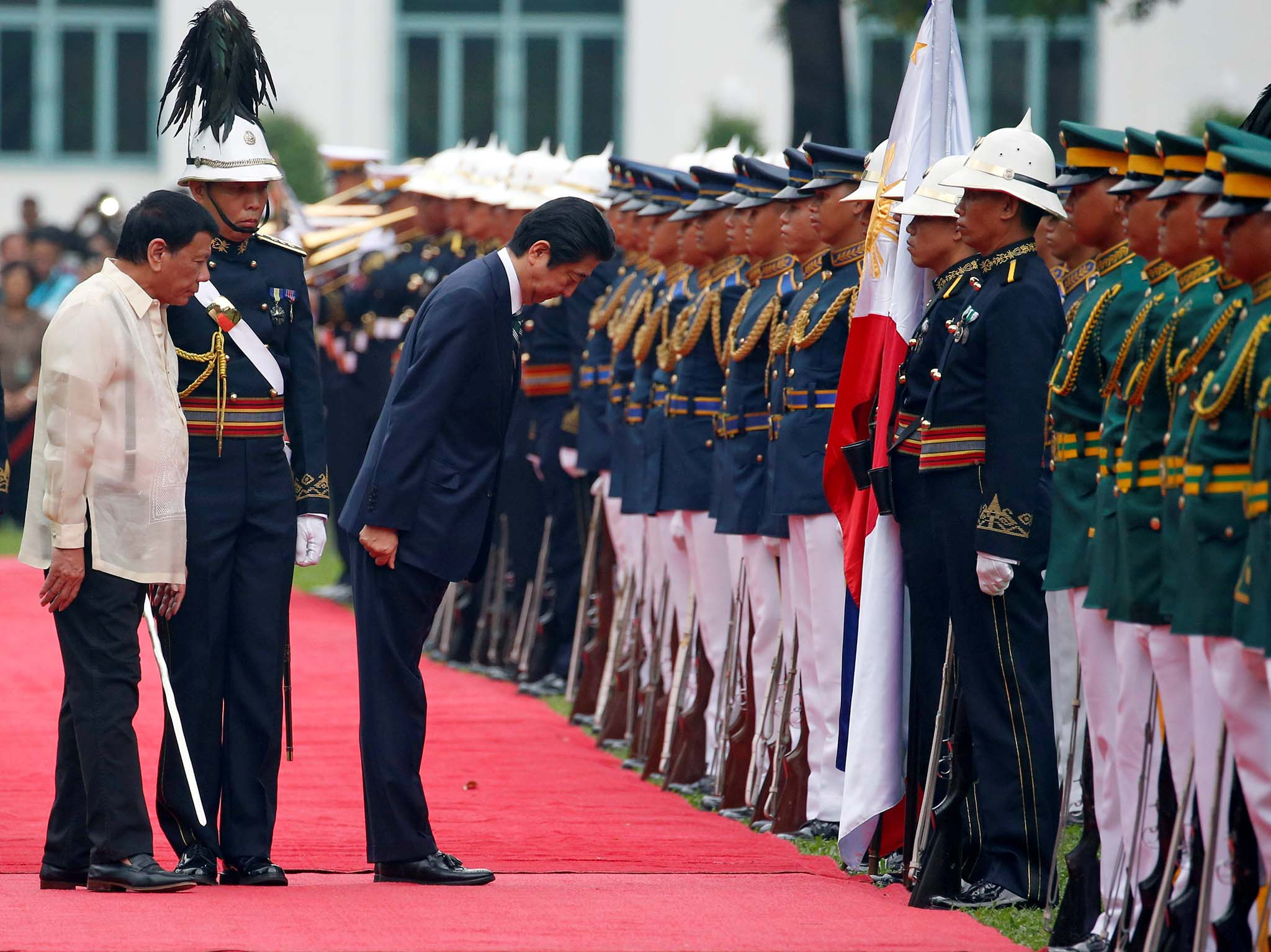 Japanese Prime Minister Shinzo Abe bows his head before the Philippine flag during a welcome ceremony at the presidential palace in Manila, Philippines